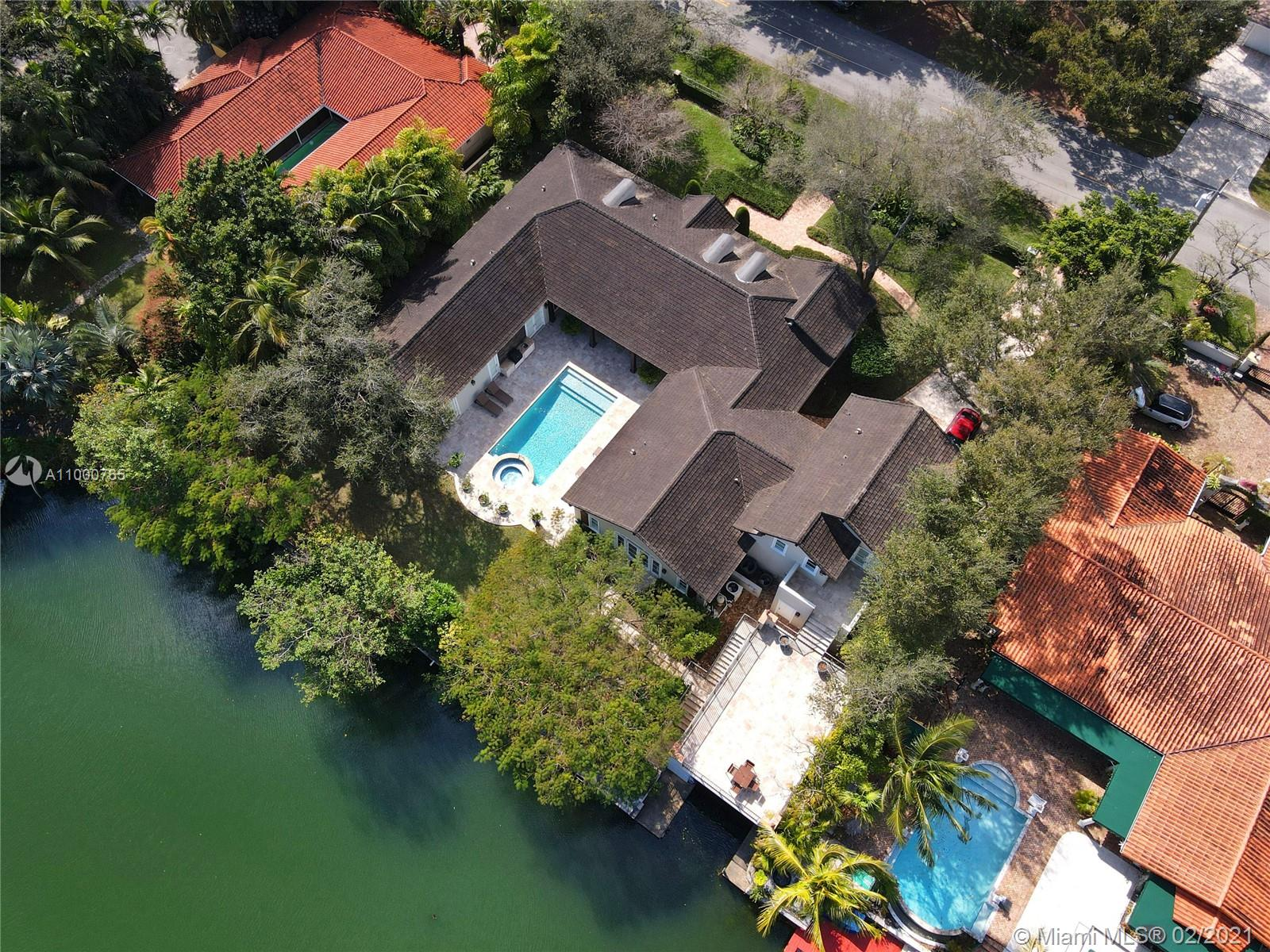 Boating or golf? Take your pick at this stunning, 2007-built & recently renovated home that is on the waterway & across the street from the Riviera golf course.  The 6 BR, 5.5 BA property, on walled & gated 24,258 SF lot w/ 150' on the water, features soaring wood-beamed ceilings, gorgeous finishes, & perfect entertaining spaces. Inside find the stunning formal liv & din rms, casual family rm open to dreamy kitchen, + BR w/ full bath that serves as a den overlooking the water!  Outside there is a deep patio, built-in grill, sparkling pool w/ spa, & boathouse w/ huge deck on top!  Spacious primary ste w/ beautiful BA & lge closet, separate guest ste, + 3 more ample BRS. Spectacular details abound: generator, mahogany front dr, impact glass, high-end appliances, & more in the best location!