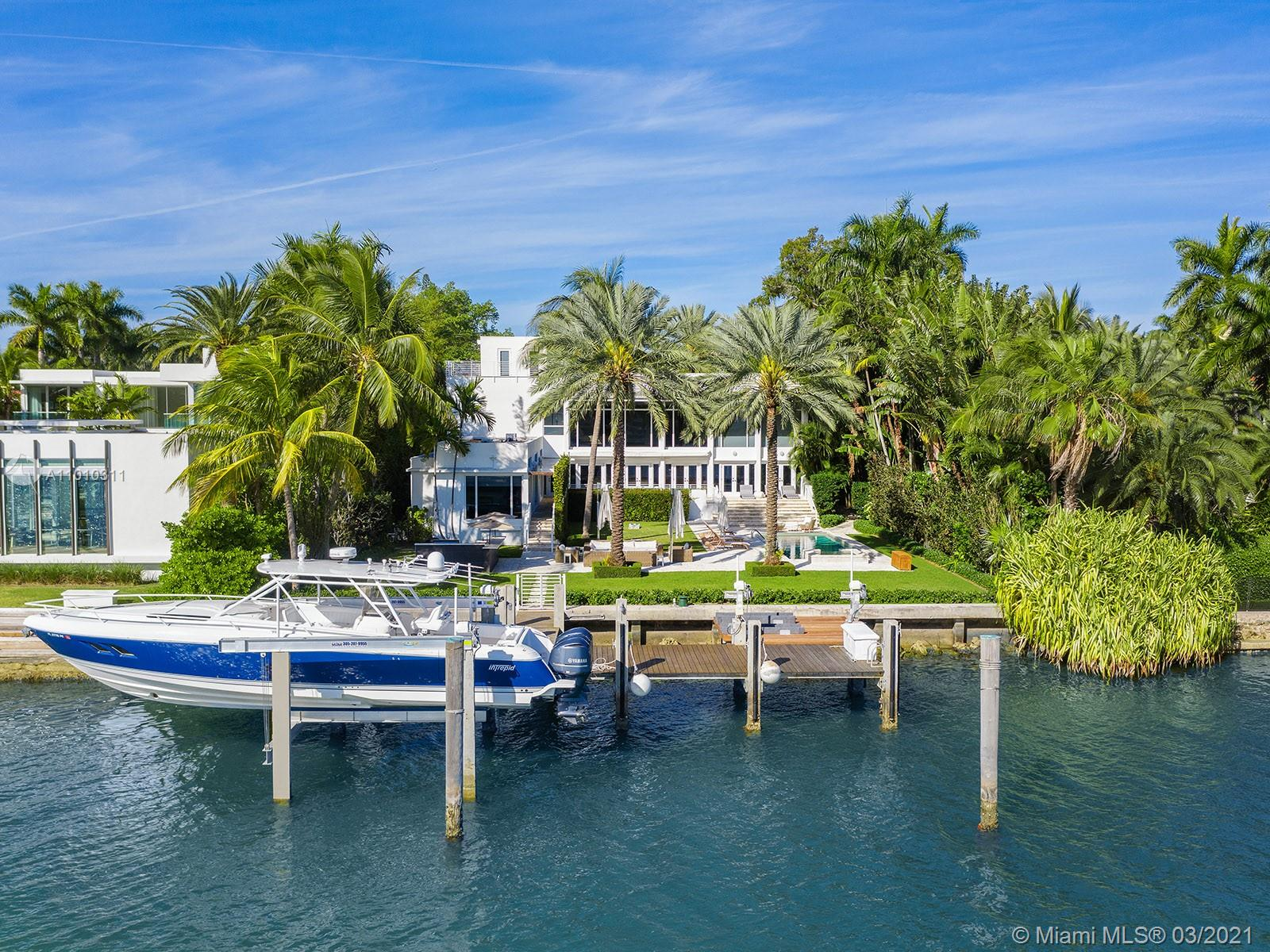 This picturesque contemporary estate is located minutes from South Beach and Downtown Miami, set apart from it all on Miami Beach's tranquil Palm Island. With 100 linear feet on Biscayne Bay, and views of the Miami skyline, the 6,995 square foot home includes a master suite spanning the entire second floor of the main house, a luxurious back yard ideal for entertaining - including pool, spa, summer kitchen, and serviced dock with lifts for a boat and jet skis - a large guest house, and a four car garage. The kitchen has been updated with Wolf and Subzero appliances, adjacent to the double-height living room, formal dining room, wet bar, and family room. Meanwhile, a discrete back stair leads to the rooftop crows nest, an ideal pertch to get away from it all while surveying your domain.
