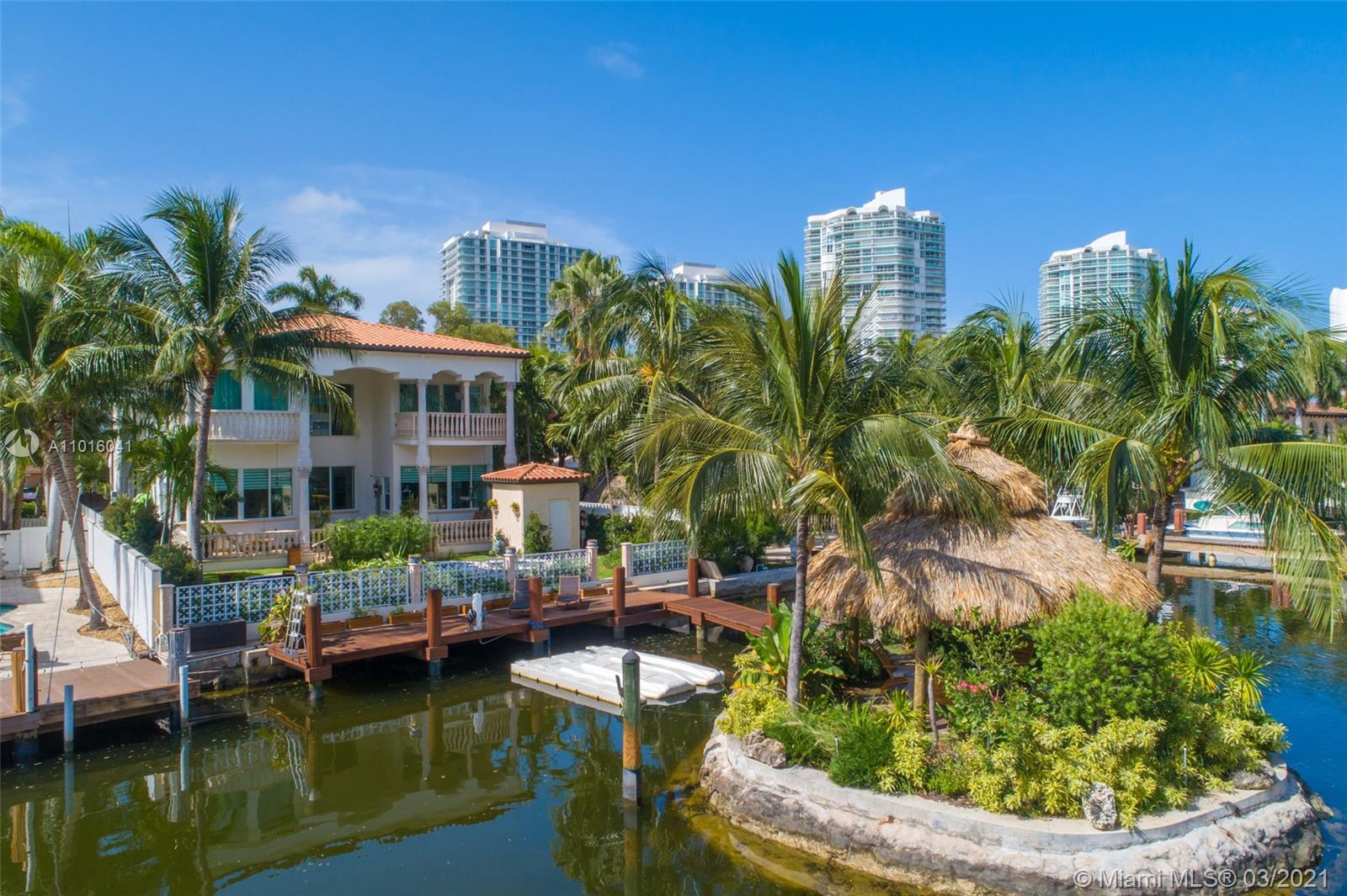 Truly an aquatic paradise, this incredibly elegant waterfront estate offers a magnificent 6,135 total SF 5bd/5.2ba floorplan situated on a 9,225 SF lot. 60ft of water frontage w/a 40ft dock + separate 2-jet ski slip overlooking the residence's secluded private island. No fixed bridges to the bay or Ocean. Additional features include: grand atrium entrance, dramatic high-volume ceilings, designer finishes, detached guest suite, oversized impact windows/doors, elevator, 2 laundry rooms & chef's open kitchen overlooking pool area. The regal double Master suites on the airy 2nd floor each offer gigantic walk-in closets, sitting areas, spa-like baths w/toto toilets & private terrace. 2-car garage, gym, & pool area w/cabana bathroom. Exclusive beach access from HOA for only $1 a day.