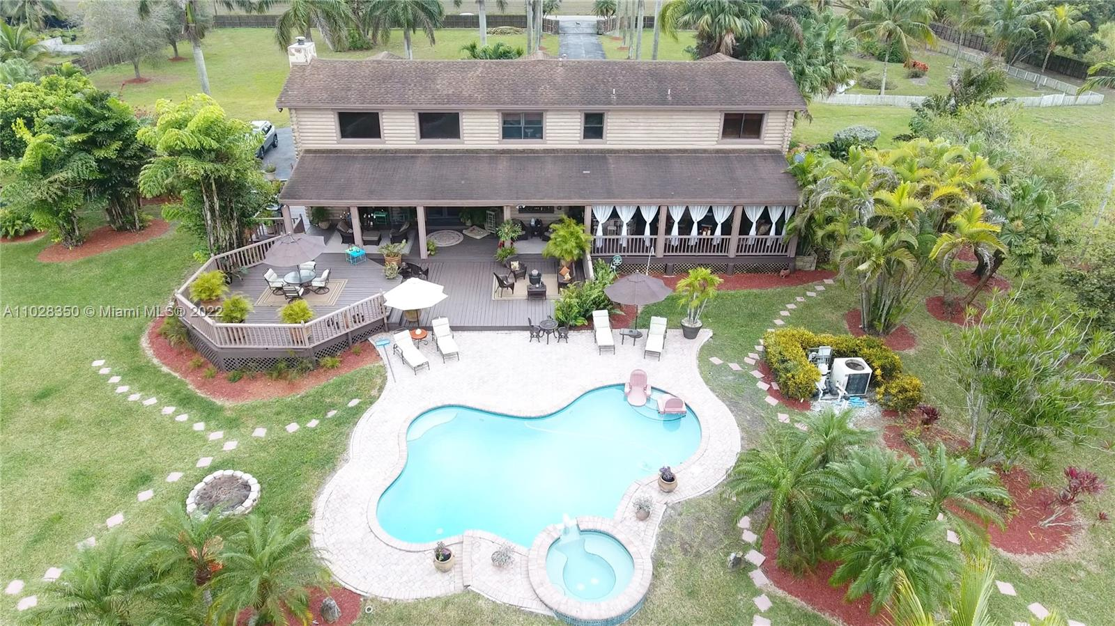5 ACRES OF HEAVEN IN  MIAMI . THIS CUSTOM LOG CABIN IS THE REAL DEAL. RIGHT OUT OF TOWN AND COUNTRY...SHE HAS AN AMAZING POND UP FRONT, 2 MASTER SUITES, A LOFT THAT CAN EASILY BE EQUIPPED WITH BARN DOORS TO MAKE THE 3RD BEDROOM.A FAMILY ROOM WITH 20 FT VOLUME CEILINGS WITH A WOOD BURNING RIVER ROCK FIREPLACE WHICH OPENS TO OVERSIZED MULTI LEVEL PATIO WITH POOL, SPA  AND BAR .A SECTION OF THE PATIO HAS EXTERIOR CURTAINS  WHICH ALLOW FOR A NAP IN THE HANGING SWING BED.. FEATURES THE 2 MASTER SUITES 1 UP AND 1 DOWN, 2 CAR GARAGE, PORTE COCHERE AND WHAT A CHEF'S CUSTOM KITCHEN!! THERES A BREAKFAST NOOK, FORMAL DINING .THIS HOME SPEAKS FOR ITSELF. THIS IS  A COUNTRY HOME LOCATED IN PRIME REDLAND. IT COULD BE AN AMAZING EVENT VENUE.
