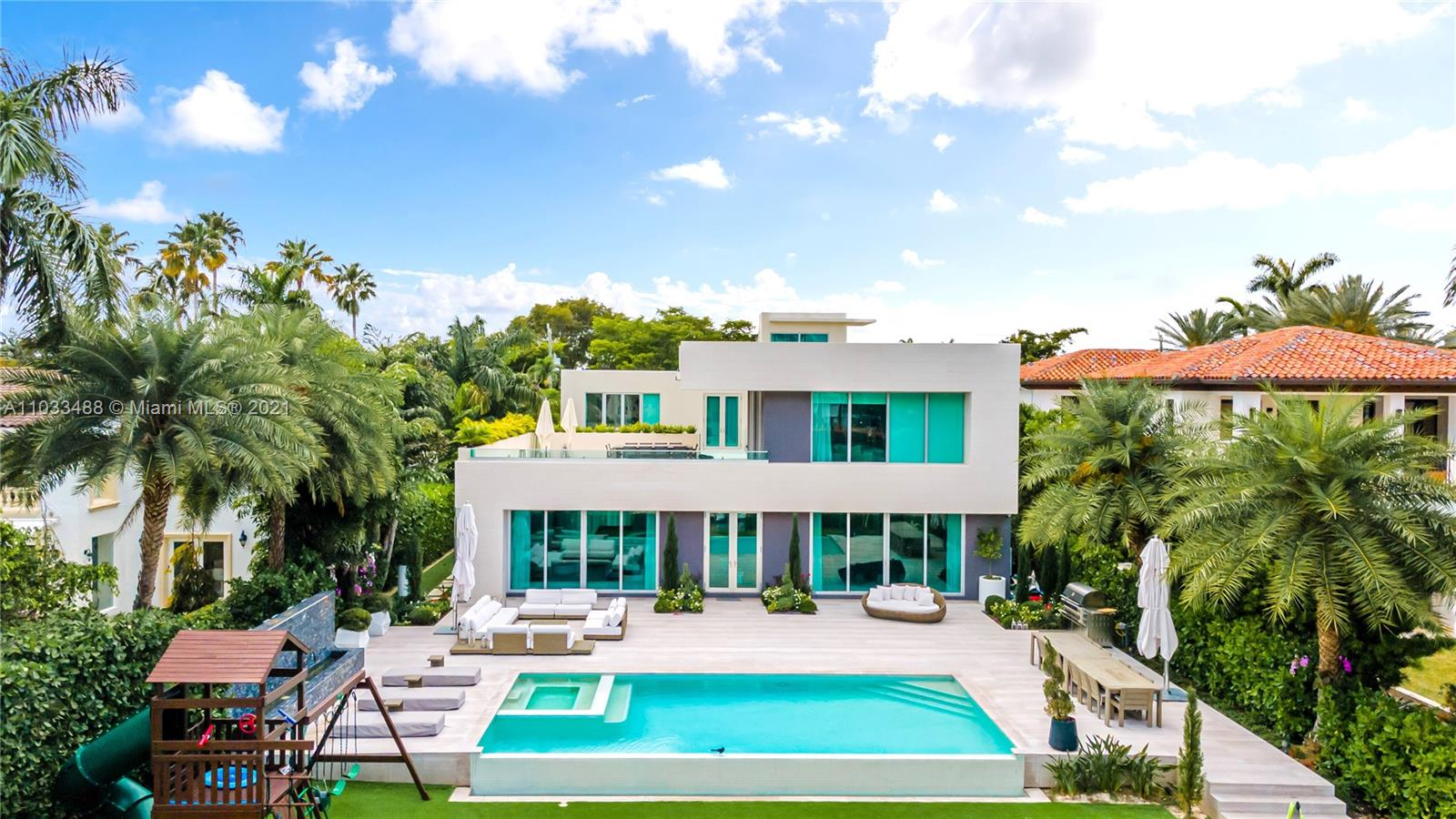 GORGEOUS MODERN WATERFRONT VILLA on Pine Tree Drive ideal for entertaining feat. over 8,000sf of living space and nearly 3,000sf of ext. living space with rooftop deck overlooking waterfront. Home features: Large Master Wing & 3 Large Guest Bedrooms on 2nd Floor, additional Guest Room Suite on 1st floor, Children's Play Room, Cinema Room, Staff Quarters & more. Gourmet Italkraft Kitchen, Wine Cellar, Wolf & Sub-Zero Appliances. Formal & Informal Living room areas with Sonos Sound system. Infinity Pool with waterfall & hot tub overlooking waterfront and lush tropical landscaping & gardens. 35' Dock with Shore Power + Bay & Ocean access with over 77ft of water frontage. Two car garage & enclosed driveway with space for an additional 5 vehicles.