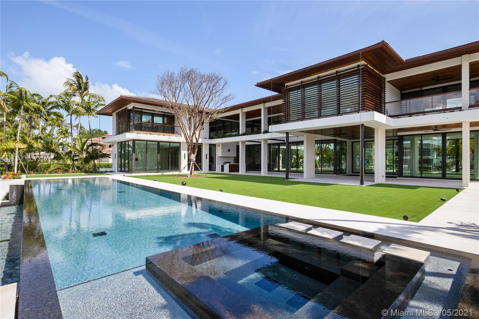"""Immediate Occupancy, Only New Construction in Coveted Gables Estates; Cesar Molina Design """"Tropical Mid-Century Modern Style"""" w/ 360 Water views; Near 1 Acre Corner lot w/ New Dock +direct shot to Ocean-No Bridges-to-Bay! 8,800 Int.SF+3700SF covered exterior spaces; 24'Hi-living rm. ceiling+ 1st floor 12'Hi ceiling; 6BR,6Bth+Nanny Rm, Gym, Media Rm+2-1/2 Bths, All top-line finishes; Cumaroo wood exteriors; Walnut Custom Kitchen cabinets, closets & doors; Quartzite Supreme Kitchen Countertops; Summer Kitchen; Laundry room; Hurricane proof sliding glass doors/windows; Shell reef ground & exterior floors; Rami stone walls; Glass railings stairs & balconies; Elevator; Electric blackout shades, Lutron lighting, Sonos Audio System, Luma Security System, Automated Gates, & Savant System"""