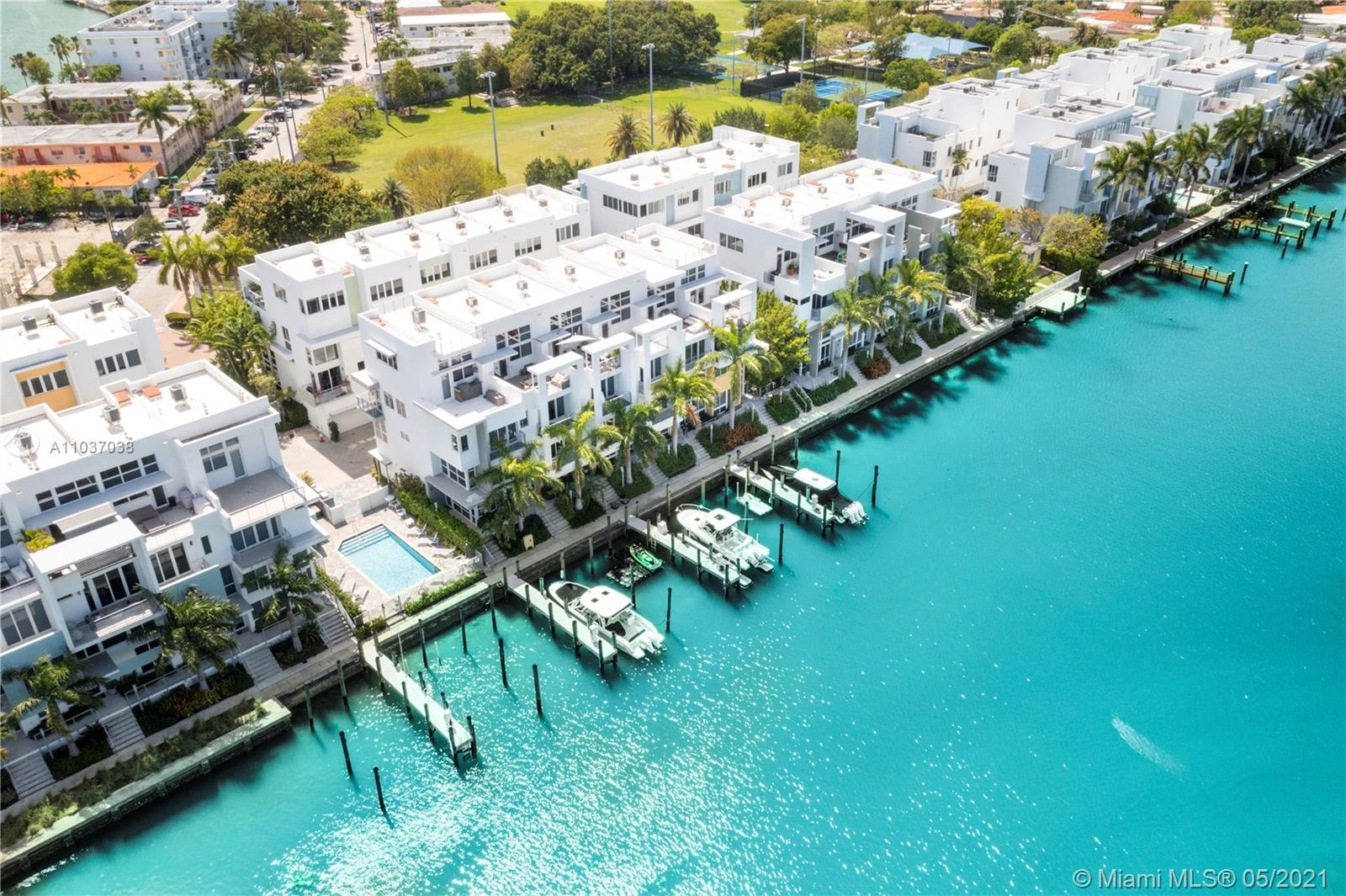 Luxury Waterfront Townhouse located in gated waterfront community of Iris on the Bay in North Miami Beach. Fully Furnished, 3 Bed plus Den/3.5 Baths, in 4 stories w/private elevator, modern kitchen, stainless steel appliances, gas cooktop, porcelain floors, double car garage w/lift for 3rd car, electric blinds, laundry room. Waterfront rooftop terrace w/TV, full outdoor kitchen, bbq & bar w/water views. Very low HOA fees. Quiet residential area. Across fully renovated Fairway Park w/tennis & basketball courts, soccer field, kids playground. Normandy Shores Golf just steps away. Walk to the Beach, supermarkets & Zagat rated restaurants. A MUST SEE!  This unit DOES NOT come with deeded boat dock but buyer can lease boat dock available for long term. Easy to show.