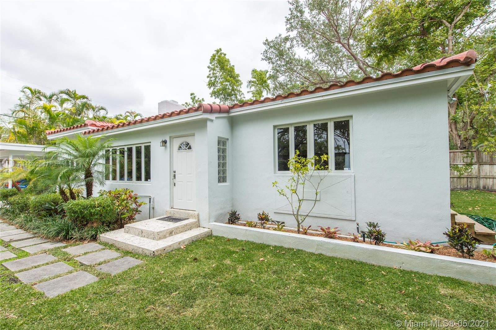 Lovely mid-century bungalow surrounded by tall privacy fence &  lush tropical garden. Located  across the street from Merrie Christmas Park, a South Florida landmark known for it's expansive grounds canopied by huge Banyan trees. This updated home features light-filled living spaces including formal dining area, wood floors, original fireplace, 2 updated bathrooms, laundry/storage room, Elfa closet systems & garden views from most rooms. Large kitchen w/ wood cabinetry & newer stainless appliances, opens to wood deck for year-round outdoor entertaining. Located in the highly rated Coconut Grove elementary school district. Close to the Grove village center's galleries, boutiques, cafes and bayfront parks & marinas. Minutes to South Miami & Coral Gables shopping & dining districts.
