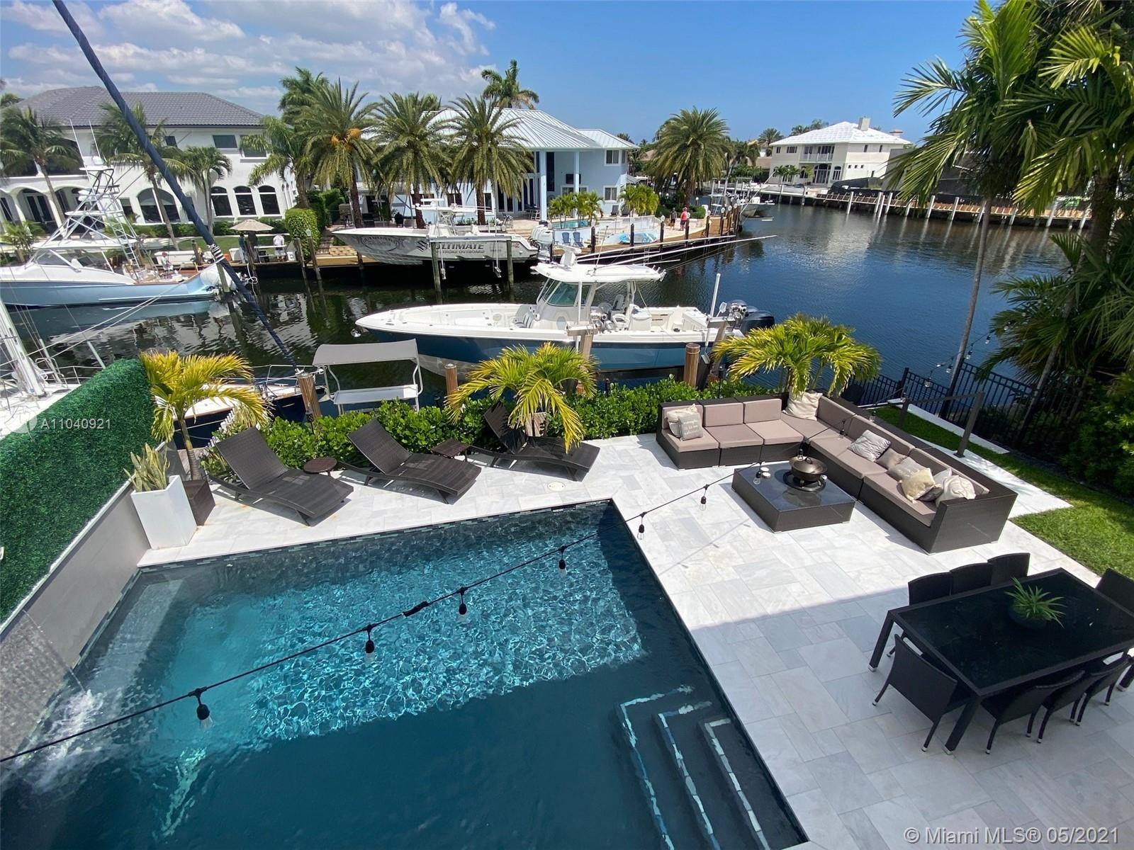 LUXURIOUS WATERFRONT ESTATE! A YACHT OWNER'S DREAM WITH 45' PRIVATE DOCK! BRAND NEW 20,000 LB BOAT LIFT AND DOCK! MODERNLY REMODELED POOL HOME is right on E Sample Road with multi-million-dollar mansions- on deep water frontage>5-8 minutes to direct Atlantic ocean access with no fixed bridges-This stunning MODERN custom residence offers the finest elements of modern architecture. Stunning new Chef's kitchen w/ custom cabinetry is open to living area & overlooking the pool & water. Master bedroom & 2 additional bedroom suites are located on the 2nd level with a large balcony also overlooking the pool & water-1 Bedroom located downstairs can be used for office or guest suite-Remodeled flawlessly!
