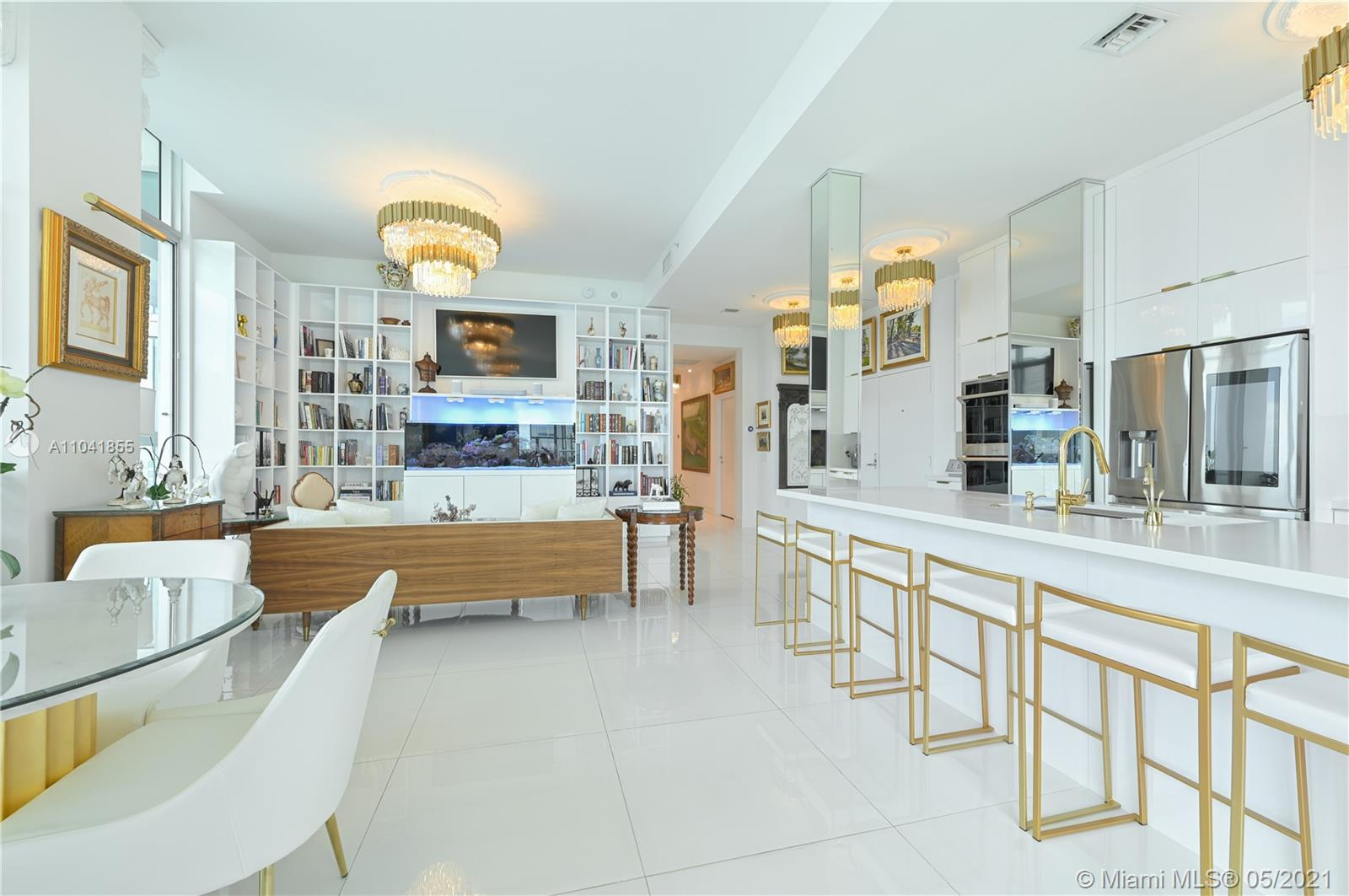 Welcome to 4006 at Met 1, where beauty and luxury meet comfort and leisure. Completely redesigned in palatial white and gold, this Downtown Miami penthouse offers a unique opportunity. Entertain effortlessly in your very own tasting room complete with custom cabinetry boasting a 100+ wine bottle cellar, built-in ice maker, sleek dual tap draft beer refrigerator, and direct access to the wraparound balcony. The stunning kitchen has been expanded and finished with high-end appliances. As you walk through the art-filled hallway, you'll encounter the impeccably designed bedrooms, each with custom walk-in closets, spa-like bathrooms, and a second balcony to enjoy privately. And lastly, this is a very rare opportunity to own five (5) designated parking spaces in the heart of Downtown Miami.