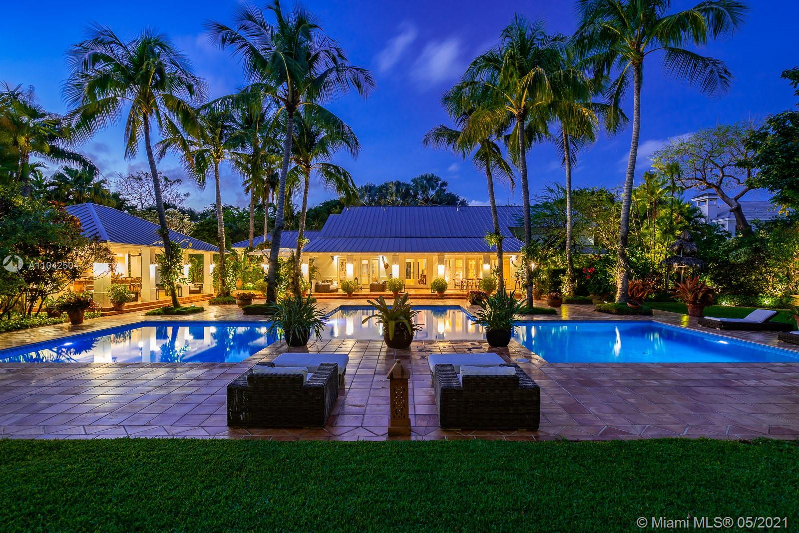 Fall in love with this extraordinary estate that is the essence of South Florida living. Magnificent interiors and splendid al fresco spaces are nestled in a vibrant flora of striking exotics. Volume ceilings, walls of glass, and splendid grass cloth coverings are the backdrop to grand social spaces which include a huge eat-in kitchen, family room w/ 1200+ bottle wine cellar, and fabulous living & dining rms. Bedrooms are glorious; each w/ ensuite bath, and the master suite is a divine spa in itself.The crown jewel of this paradise is the outdoor oasis of covered verandas, resort-style pool, remarkable summer kitchen, and breathtaking canopy of color. One could never imagine what lies beyond these gates, and PS, there is a 3-car garage w/ air-conditioned gym and a full house generator too!