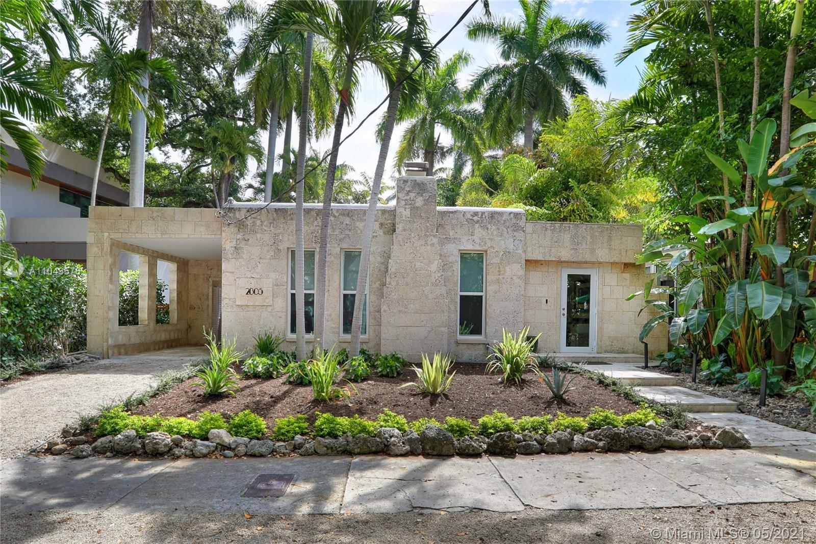 """Unique """"Oolitic Limestone"""" bungalow on a quiet, tree-lined North Grove street. Totally rebuilt by the current owners (completed 2021) to create a blending of the charm of Old Miami with a modern, minimalist vibe. Light-filled, open living spaces w/ original fireplace, custom built-ins, volume ceilings & beautiful wood flooring throughout. New, European-style kitchen features quartz countertops, stainless appliances & breakfast bar. Luxurious, tumbled marble bath offers an oversized, frameless glass shower. Spectacular outdoor space is an ultra-private, tranquil oasis with heated pool & spa surrounded by lush tropical landscaping. Close to the Grove village center's galleries, boutiques, cafes and bayfront parks & marinas. Minutes to downtown, MIA, Coral Gables, Key Biscayne & the Beaches"""