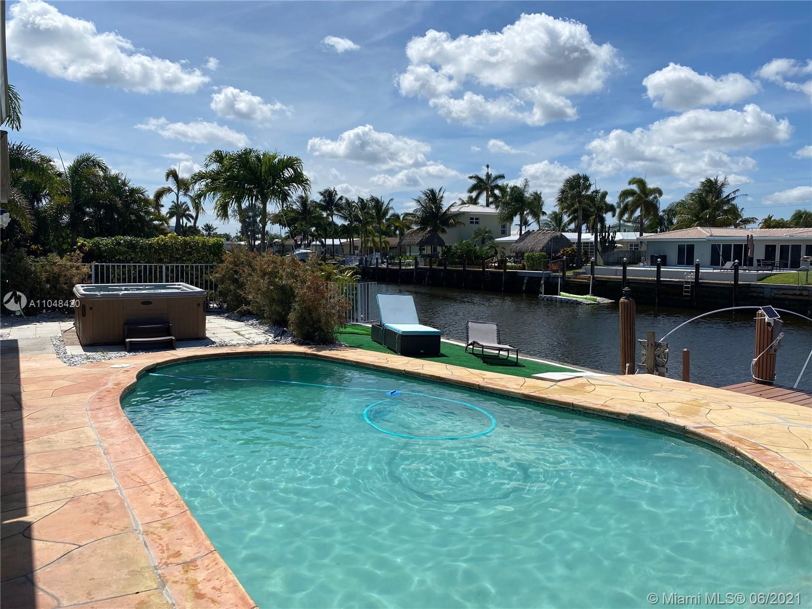 PRIME LOCATION on the Intercoastal Waters (Pompano Canal) within a 20 minute boat ride to the ocean. LARGE 70 ft private dock access. This stylish home has an open floor plan in Garden Isles (minutes to Fort Lauderdale) that comes with large living space and large rooms: 3 bedrooms, 2 full baths, Living Rm, Family Rm, Large Laundry Room, New Shed, New Pool Heater, BEAUTIFUL PRIVATE OASIS HOT TUB, private pool, mini putt golf, screened in patio, large circular driveway (can easily park 6 cars), security cameras, keyless entry, nest thermostat, modern lighting fixtures, 2 car carport with storage closets, and gorgeous views. See video.