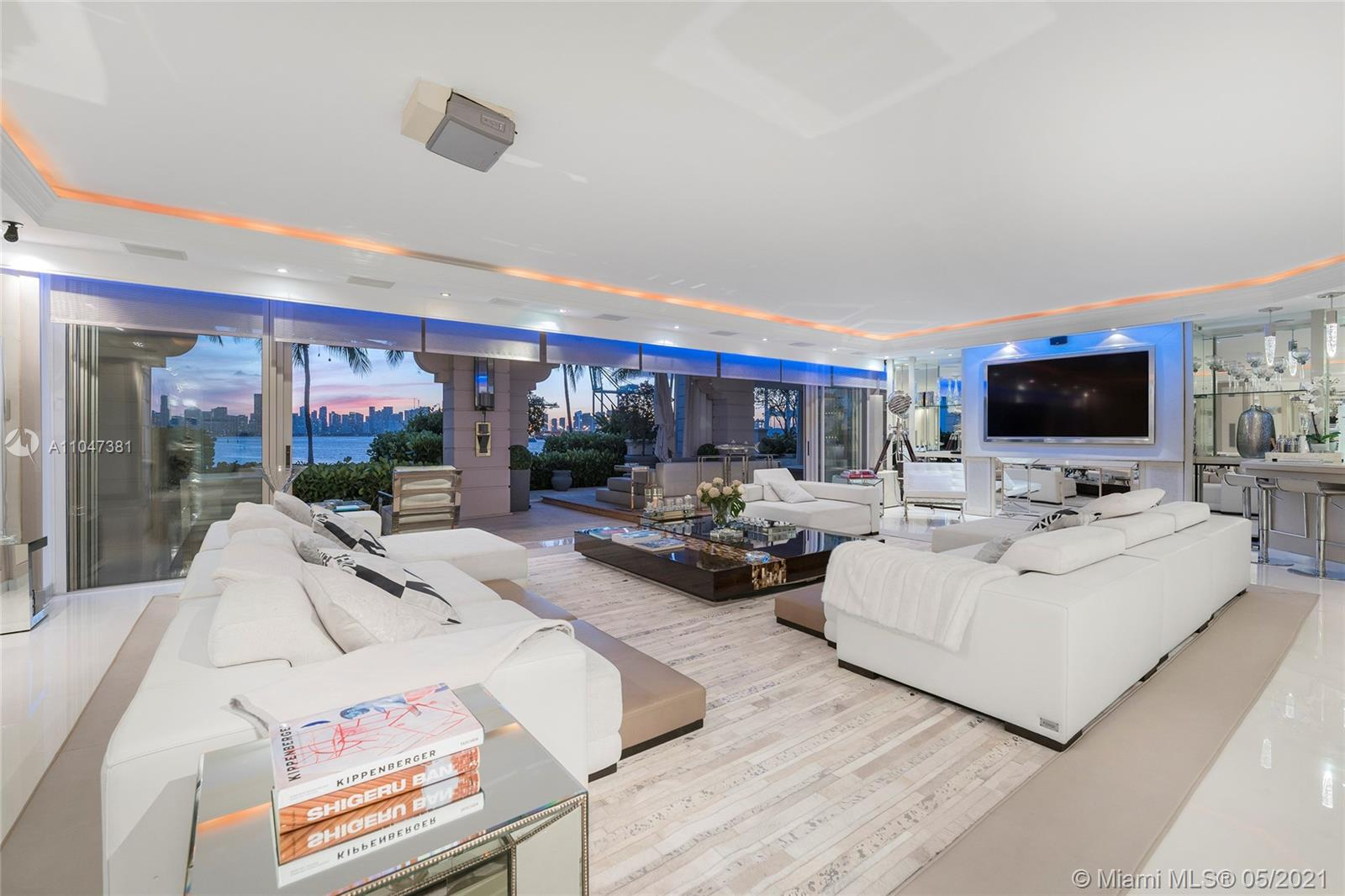 This coveted ground floor Bayview unit offers the best of Fisher Island with unobstructed views to Biscayne Bay & Downtown Miami Skyline, plus amazing sunset views. The 5BR/5+2 BA unit features 6,260 SF, exquisite white porcelain floors, FENDI designed wallpaper & doors plus a built-in surround sound system. Spacious open living room w/wet bar & dining room both w/direct bay views. Amazing Chef's kitchen sports top-of-the-line Miele & Sub-Zero appliances, eat-in center island, butler's pantry & breakfast area. Private bayside principal suite offers tan oak floors & bathroom w/dual walk-in closets, glass rainshower & a sunken spa tub. Expansive bayside terrace w/multiple seating & lounging areas, al fresco dining table & arches that frame stunning views to the bay & Downtown Miami skyline.