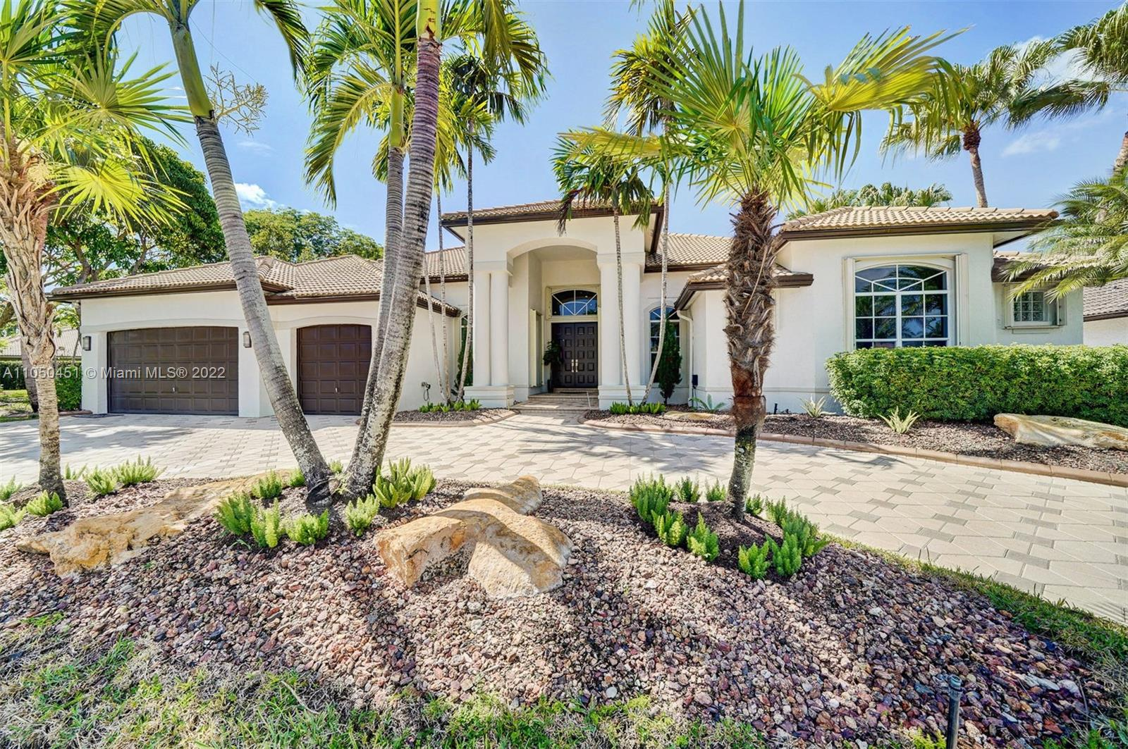 """This pristine, COMPLETELY REMODELED IN 2018, 1-story modern/contemporary home is perfectly set on a 16,504 SF lot. Situated in the prestigious Weston Hills CC """"POINCIANA"""" featuring 5BDS/5BATHS/Den/Office/Large family room perfect to create 2 ambiances, 3-car garage and a circular driveway. The master suite features wood floors, a sitting area + an office, and 2 walk-in closets. The kitchen features stainless steel appliances, white siltstone countertop & glossy cabinetry. The spacious breakfast area looks out to a serenity lake and a pool. All bathrooms feature new tiles, glass shower doors, and new vanities. The high ceilings give you a sense of space. Smooth textured walls, marble floors. Led lighting system, 3 AC units 2019,  accordion shutters throughout & Custom Closets and cabinetry."""
