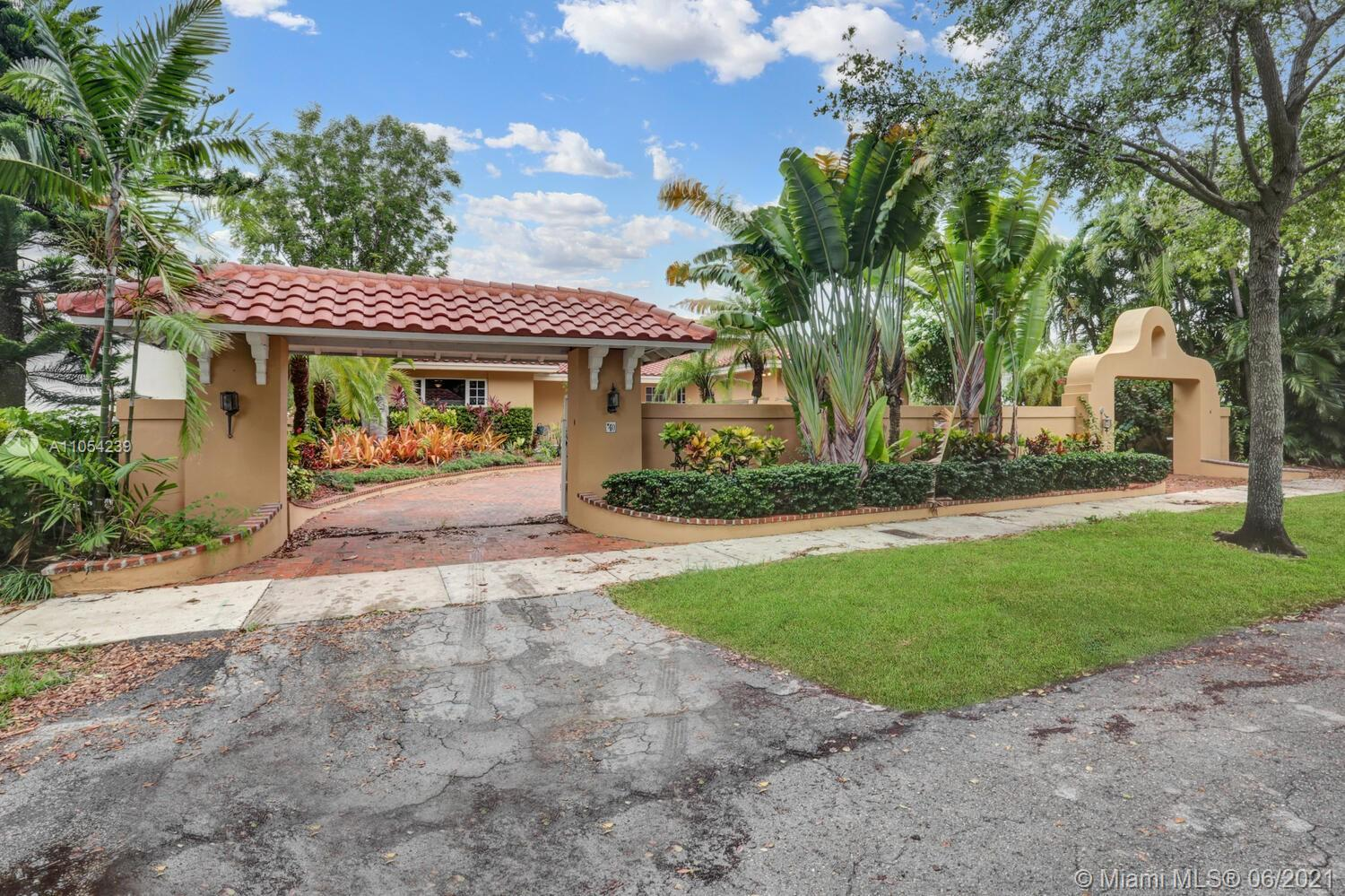 This large home is behind a high wall and has impact windows, 2 garage spaces and a covered terrace with an off the pool bar. The circular driveway has 2 electric gates at each end. This large home offers 24-hour security and is not located in a flood zone. An open floor plan that allows you to see the huge backyard. (14,321 sq.ft. lot) and the pool as soon as you enter. High ceilings with a very comfortable and enjoyable living room and family room. A huge master bedroom with its own dressing room and bathroom.