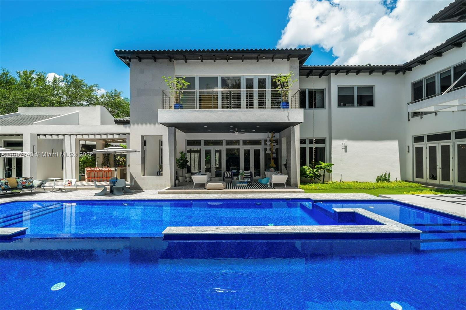 Glamorous contemporary living in Ponce Davis. This 10,267 Sq. Ft. home, with 7 bedrooms, 7 full and 2 half bathrooms, features open balconies throughout the second floor, high ceilings, tall windows, and French doors allowing seamless integration of the indoor living spaces and outdoor terraces. State-of-the-art floor plan includes an open family room and beautifully appointed chef's kitchen with Miele and Gaggenau appliances. The main suite, with seating and an office area overlooking the gardens, has a sumptuous spa-like bathroom. Superbly designed and manicured grounds include a sparkling pool with wave pump, covered terraces ideal for entertaining, full summer kitchen, and separate fitness room. This magnificent home balances style and comfort, perfect for today's lifestyle.