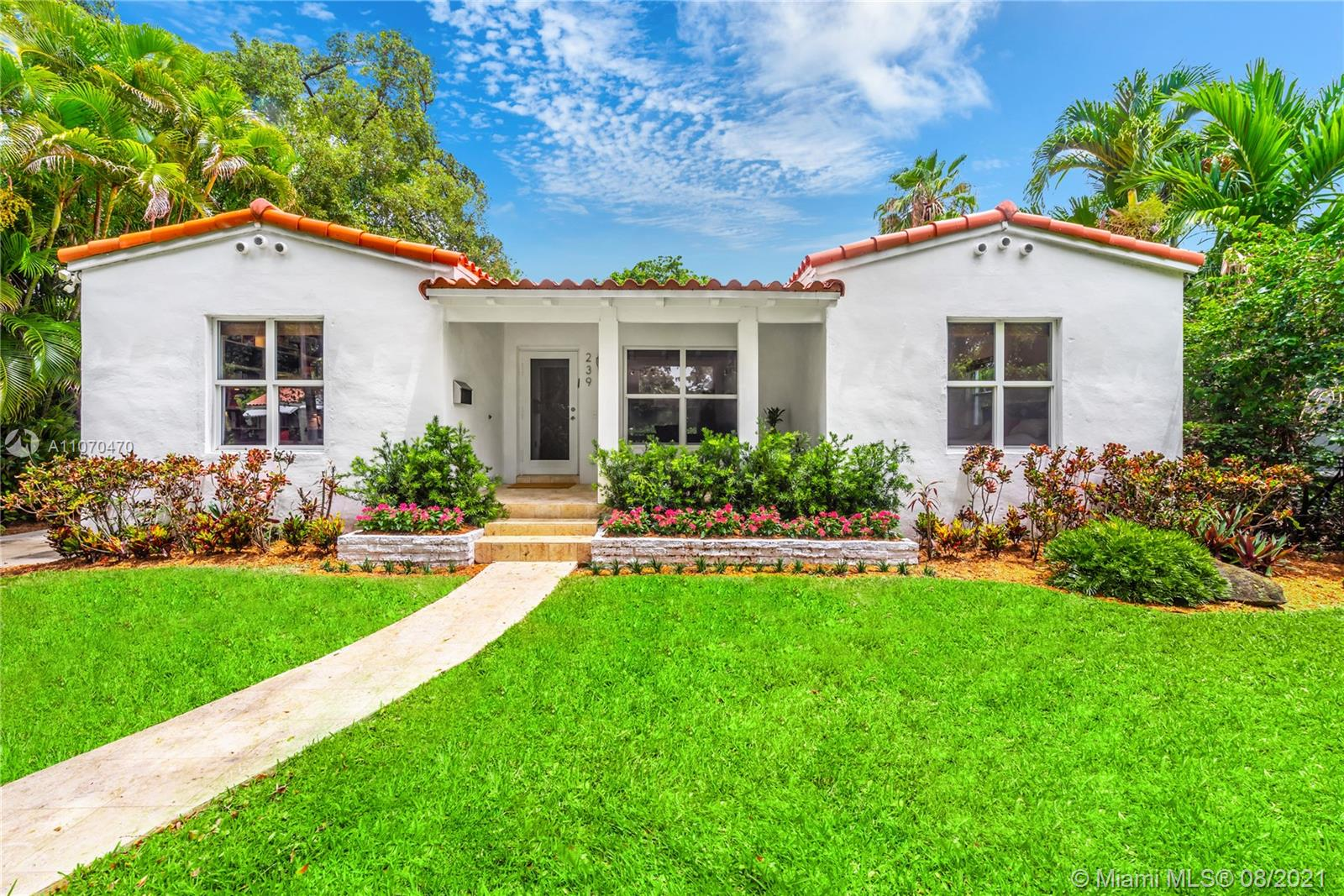 Charming Coral Gables ranch-style home! Walking distance to Merrick Park, Plaza Gables, or CG Youth Center. Welcome to your quiet urban oasis, wake up to birds singing. The lush backyard and picturesque front entry allow for gorgeous garden views from every room. Inside, you will find fully updated features including a modern kitchen, 3 bedrooms with en-suite bathrooms, & recessed lighting. The welcoming front porch leads to an open layout with restored original wood floors bringing warmth into the home, while terra cotta tiles seamlessly connect indoor & outdoor spaces. Extra features include large laundry room, full impact windows/doors & attached storage area. Ideal location blocks from Miracle Mile & Metrorail; a short 15 minutes to Miami International Airport and Brickell.