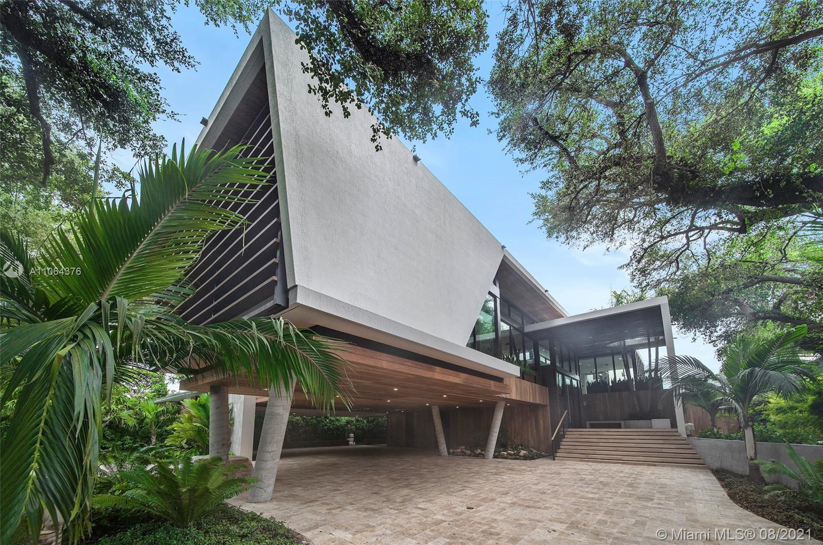 Spectacular Tropical Modern masterpiece set within a lush botanical garden behind a custom coral rock garden and gate. Designed by acclaimed architect Gabriel Lopez. The quality of finishes, fixtures, and attention to detail is unsurpassed by any new construction home in Coconut Grove. Double-height ceilings and walls of glass create a seamless blending of interior and fabulous exterior spaces. Custom kitchen by Bontempo. Smart Home automation. 2-electric car charging stations. 24/7 security patrol. Live amongst the elite on the exclusive residences behind Vizcaya Gardens. Minutes to downtown, Brickell, and the Beaches. Total 16,304 SF; Adj 9,753 SF