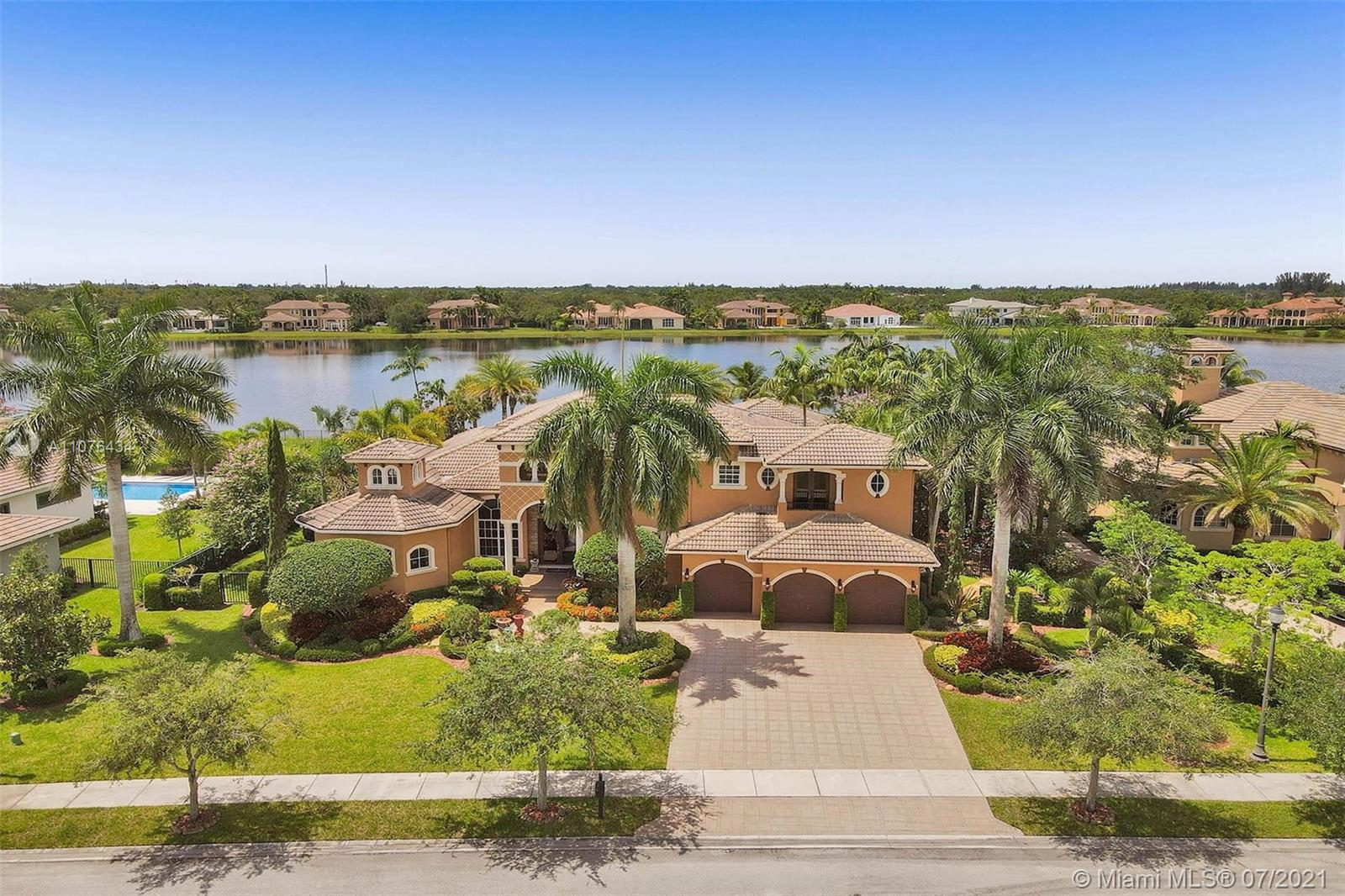 Elegant custom-built Vanderbilt model tucked in the 24 hr guard-gated community of Windmill Reserve at Weston.5,442 square feet under air. Sitting on over a 1/2 acre of lushly landscaped serenity with deep and wide lake view, scenic pathways, and fully fenced with sparkling infinity-edge pool and spa. Enjoy immaculately maintained and spacious 5 bedrooms+office+game room, 6 full baths & 3 car garage. Owner's suite on the first level with sitting room. Luxurious marble owner's bath. Marble and wood flooring throughout living areas. Grand staircase to the second level. Summer kitchen with large patio overlooking the peaceful and beautiful green and garden areas.