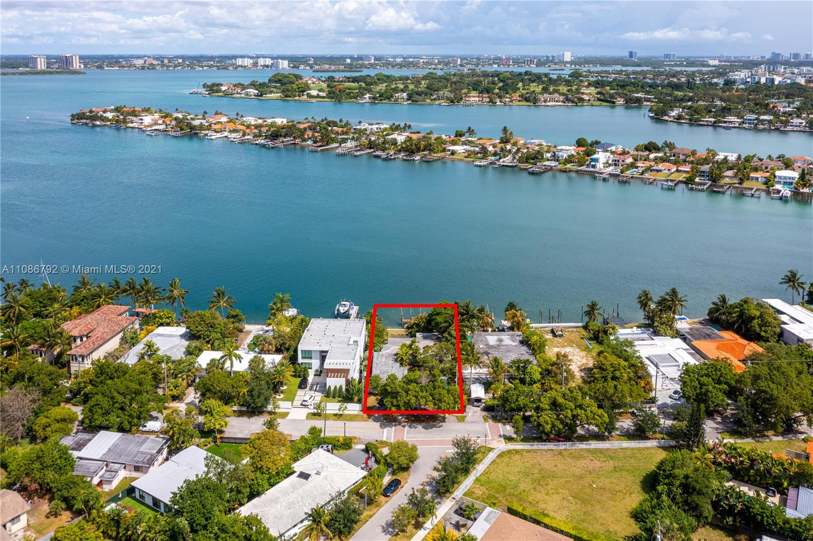 Classic 1950s Waterfront home located on guard gated Biscayne Point Island. Bright, open, and spacious with a total of 4 bedrooms and 3 baths, plus  2 car garage on an oversized 11,250 SF lot with 75 Ft on the water, perfectly positioned to maximize the wide bay views.   Eat-in kitchen, formal living and dining, plus waterfront family room surrounded by floor to ceiling glass sliding doors.   Update, renovate, or recreate to build your dream home in a desirable and secure location. Ideal for boaters too with dock, wide water open bay  access, and no fixed bridges!