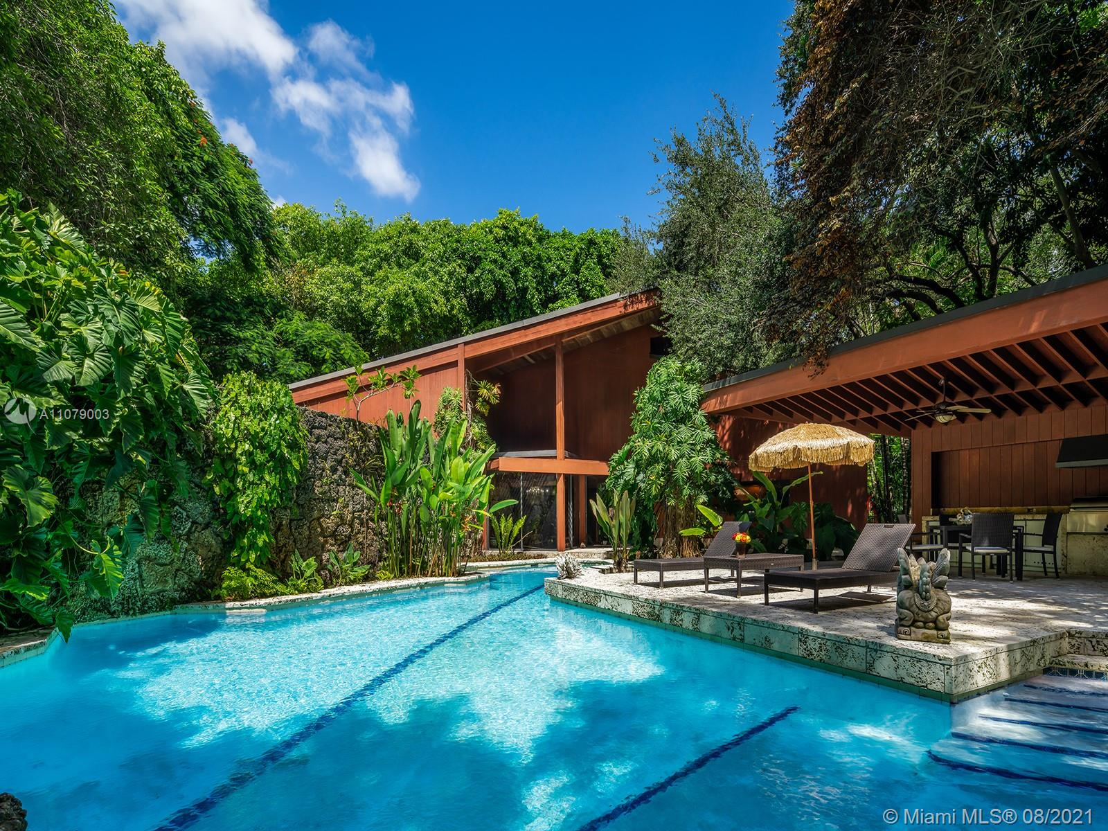 """This iconic Ponce-Davis home, designed by renowned Miami architect Chayo Frank as his personal residence, embraces the natural jungle environment that surrounds it, creating a truly unique and one-of-a-kind house which could not be built anywhere but South Florida. With a skeleton of structural steel beams encased in California Redwood, the 5,000 square foot house's vast living room features large windows looking out onto a richly planted garden of tropical and subtropical species. Built in the """"organic"""" architectural style of Frank Lloyd Wright, the house features a freeform pool with 50-foot lap lane, paths winding around coral rock grottos, many terraces, a double-height master bedroom, an impressive guest suite, and a tree-house-like office accessed by ladder."""