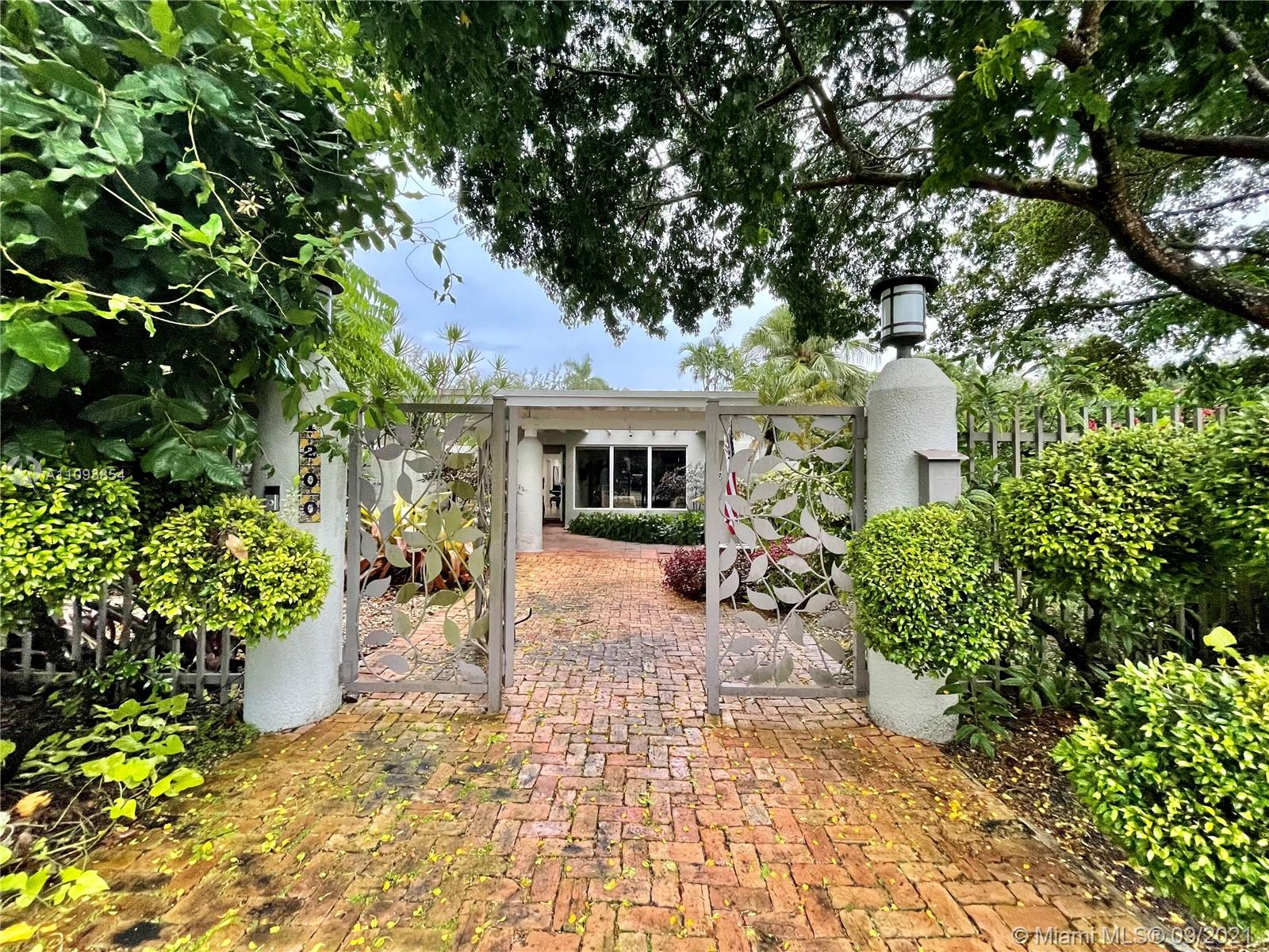 Gorgeous private peninsula home on approximately 18,000 sq ft lot, surrounded by luscious landscaping on desirable S Alhambra Ave in Coral Gables.Modern Key West style metal roof, 30 solar panels, impact windows and doors, and much more. This property has enough space to built a guest house and pool.