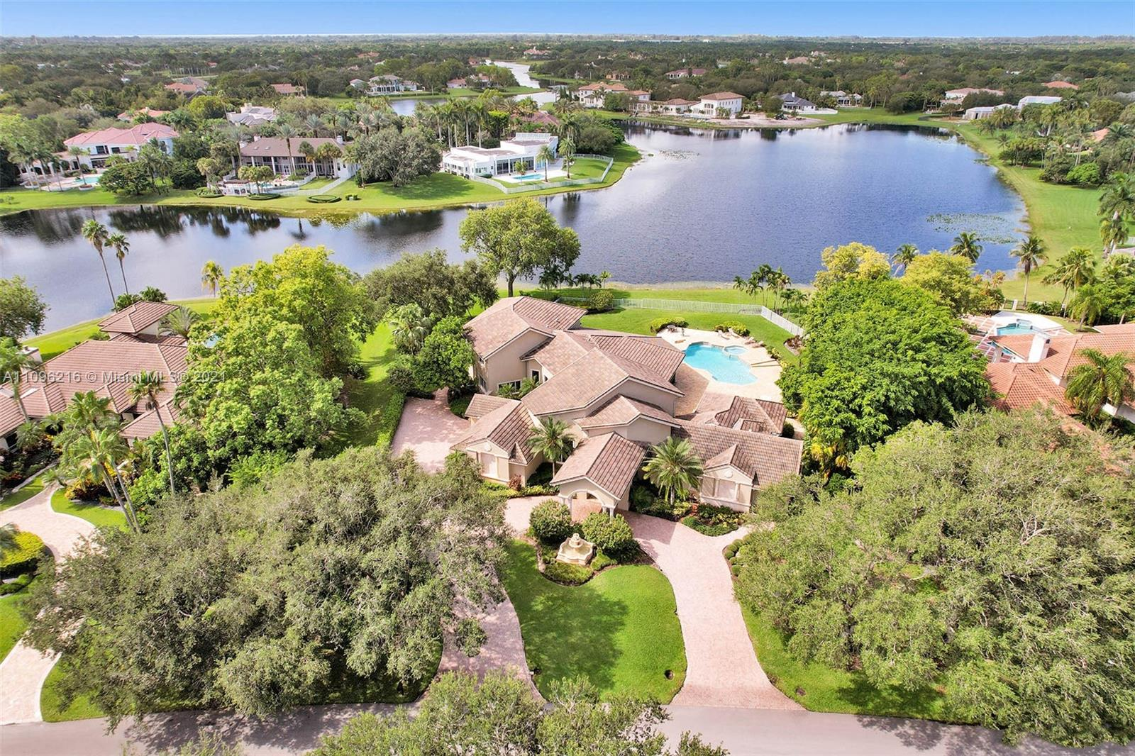 Absolutely spectacular, one-of-a-kind estate located in the prestigious community of Windmill Ranch Estates. This pristine residence includes: grand circular paver driveway with porte cochere, open dining room & living room with breathtaking lake views, master bedroom suite with sitting area, office, exercise room & luxurious bath, gourmet kitchen with center island & every beautiful detail imaginable, the family room & breakfast area open perfectly to the billiard room with bar, 3 bedrooms downstairs, 3 bedrooms upstairs with a large loft, incredible wrap around screened patio with summer kitchen to enjoy South Florida living at its finest along with sprawling outdoor patio areas perfect for entertaining around the oversized pool & spa, perched high on a 1.33 acre lot with a 3 car garage!