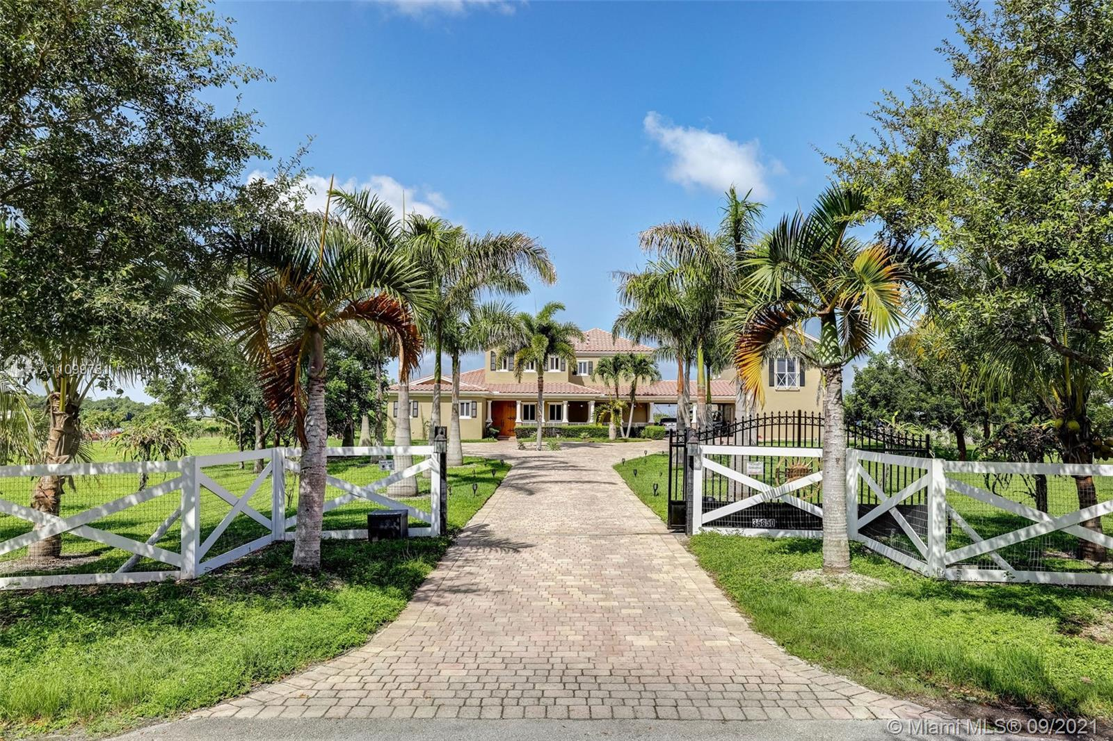 Love horses, endless space & skies? Boating & fishing? Chilling & relaxing? This home fulfills many dreams. On 5 acres in a gated community with 250 income producing fruit trees (approx. $ 30K), it is located just 30 minutes to Key Largo & 45 minutes to downtown Miami, MIA & many dining- shopping districts. Everything is centered on Florida outdoor living – huge, covered patio to enjoy tropical vistas & a large pool with a swim up Tiki bar! Invisible dog fence, mosquito repellant system, vegetable garden ready to be planted. High ceilings & flowing living spaces all opening to the patio. Master suite is located on ground floor & 4 bedrooms on the 2nd floor.  All impact windows & doors, a propane generator & a fabulous coach house above 3 car garage with a full 1bedroom apartment