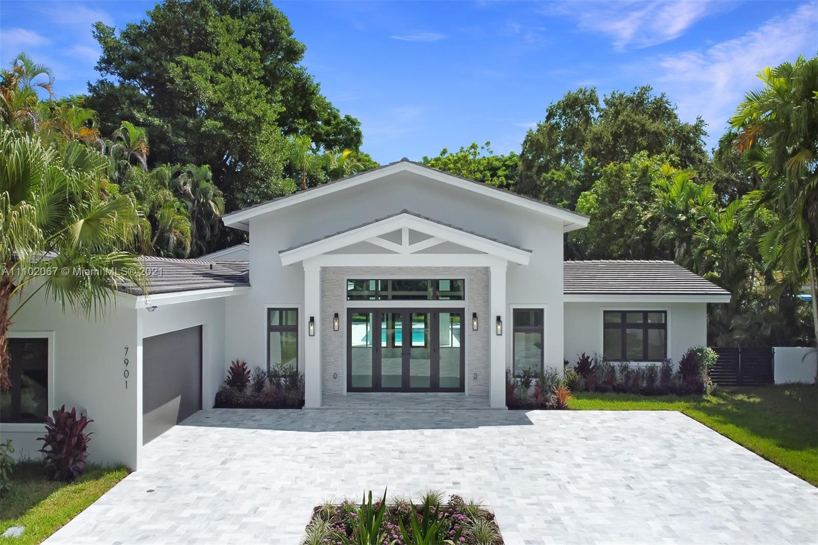 Spectacular 1-story estate located in Coral Gables' Platinum Triangle. Offers soaring ceilings, 6 beds, 7½ baths, and is nestled on a 20,000 sf lot surrounded by lush tropical gardens and mature trees. This 5,267 adj. sf (6,290 total sf) residence was fully gutted and rebuilt in 2021. Everything is new: roof, floors, walls, impact windows, plumbing, electrical, HVAC, septic tanks, kitchen, laundry room, baths, and driveway. Featuring a top-of-the-line kitchen with huge island, Sub Zero and Wolf appliances, wet bar, breakfast area, and walk-in pantry. The luxurious main suite has a sitting area, his and hers walk-in closets, a spa like bath with double showers and a floating tub. The heated resort style pool and spa, summer kitchen, and shaded outdoor terraces are perfect for entertaining.