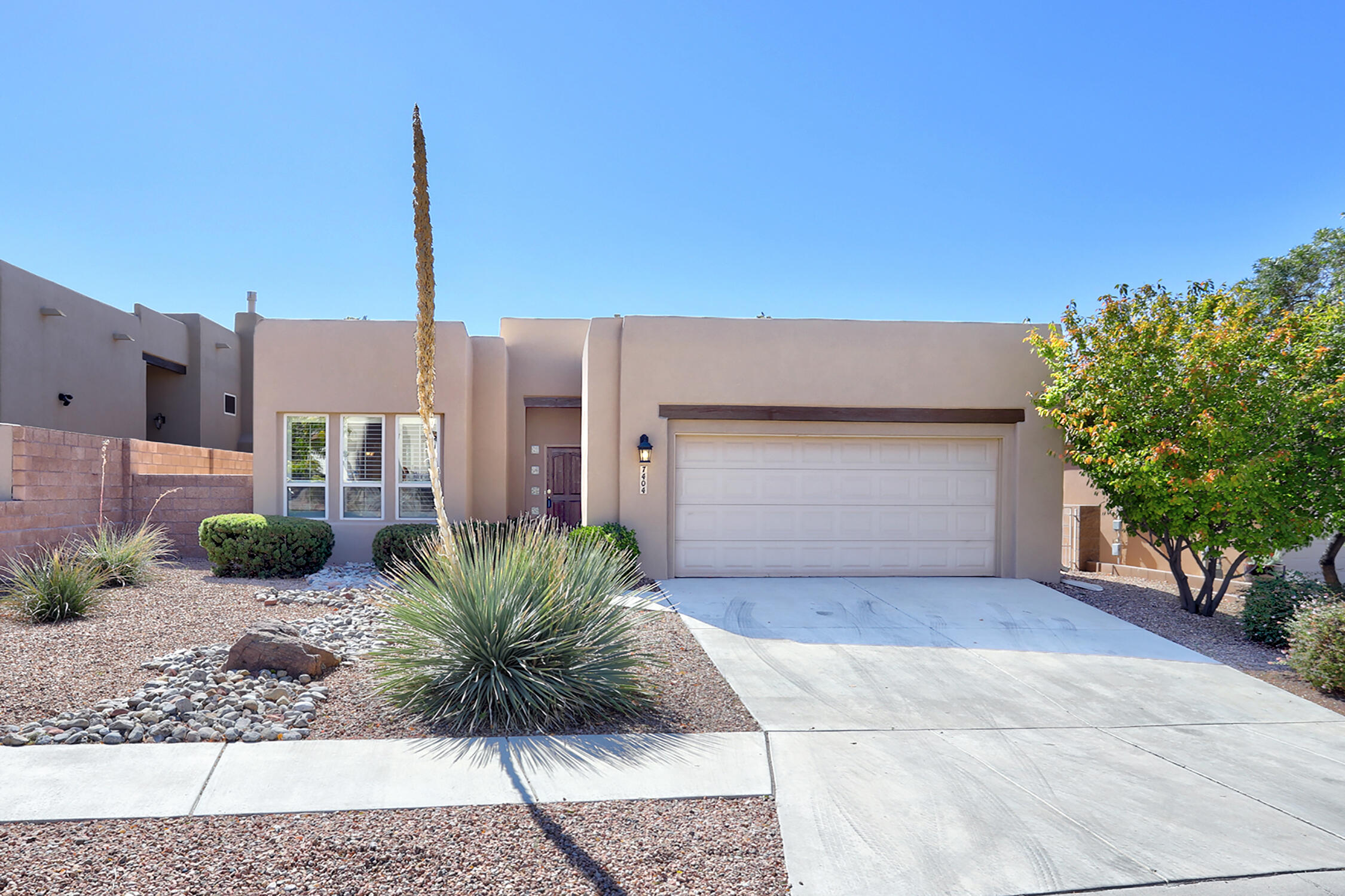 A one story home in gated Desert Ridge Trails community was built by Scott Patrick. This home is where Pueblo style meets contemporary with raised ceilings, & geometric cut out accents. Freshly painted in a modern neutral tone with clear story windows & sky lights bathes this home in light. Large kitchen with ample counter & cabinet space, with an island, pantry & breakfast area. Generous size great room has a rounded wall of windows, a fireplace, & is open to the dining room perfect for the holidays. The Primary suite oasis has recessed ceilings, double sinks, garden tub, separate shower, & huge walk in closet. Back yard sanctuary with covered patio, flag stone paths & mature shade trees. Newer stucco, TPO roof & tankless hot water heater. Located in North Star & La Cueva school districts