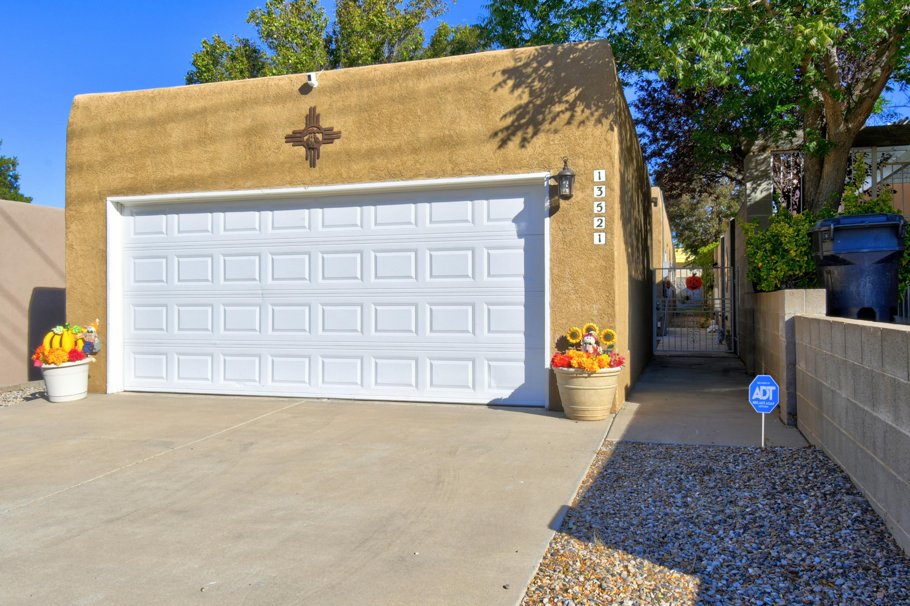Beautifully cared for home in the NE heights! Beautiful kitchen with custom cabinets and granite counter tops.  Open to spacious living area with cozy kiva fireplace. Three nice sized bedrooms and two full large bathrooms.  Maser has good sized walk in closet with sliding door to private backyard with covered patio including exposed vigas.  Only detached home on street with privacy all around.  Once you arrive in the garage you are fully enclosed in outside living space that leads to home.  Beautiful wood laminate and tile throughout.   New refrigerated air to keep you cool in the hot summers and the kiva fireplace to keep you toasty in the cold winter months! Come see this home. It will not disappoint!