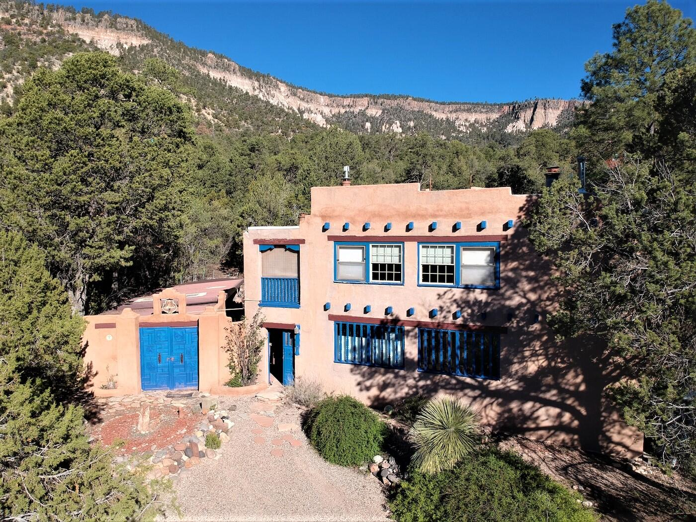 The Sweet Style of Santa Fe...in the Jemez Mountains!! Just North of the Village of Jemez Springs & just up the road from Soda Dam, this home is waiting for you to make it your dream come true! Upper & lower level, each its own contained living area, complete with kitchen. In-Law quarters? Rental (You live in one and rent the other). Two family share? VRBO? All possibilities! Beautiful artistic touches, custom tile work & amazing hand carved wood doors & trim.  So many amazing spaces with so many options! Sweet partially covered deck to take in those views. Shaded Portal becomes summer living space! Separate 370 sq ft studio. Amazing meditation space! Even a star gazing platform!! Most Furnishings can stay. All on almost an acre of Heavenly Jemez! This is one of those you just have to see!