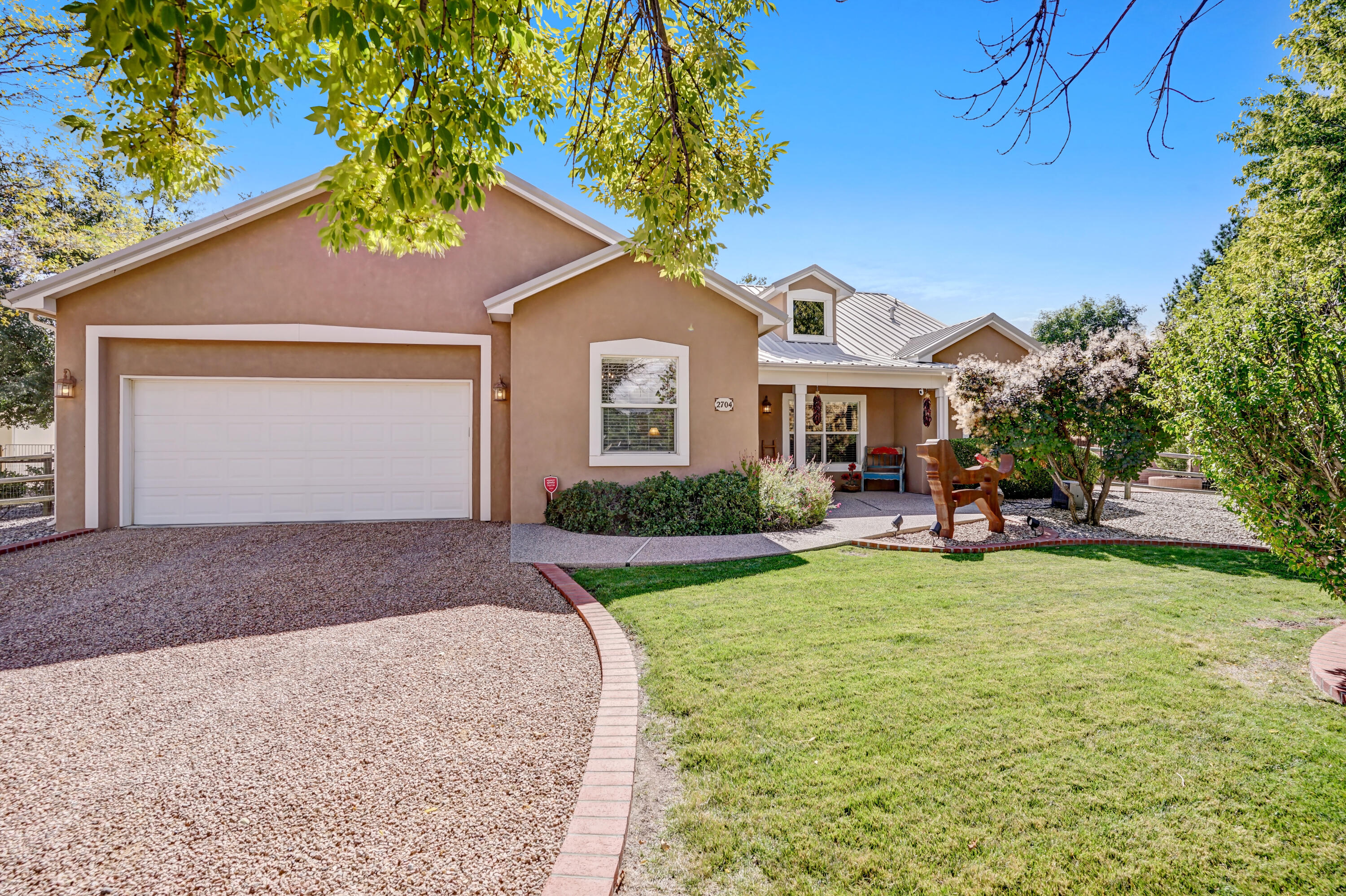 ABSOLUTELY BREATHTAKING home with classic Northern New Mexico style tucked into a quiet cul-de-sac of this private and peaceful neighborhood with Bosque trail access. Immaculately maintained inside and out, you will fall in love with this West River Valley beauty! Cathedral ceilings, skylights, and warm hues make this space light and bright with a chic southwestern charm. The chef-ready gourmet kitchen is highlighted by granite countertops, backsplash, double ovens, walk-in pantry, and a choice breakfast bar.  Cozy up to the Anasazi accented Kiva fireplace on cool evenings or relax with a book or Netflix binge in the laid-back second living area!  Framed by a gorgeous yard with gentle grass, shady trees, tranquil water feature, kiva, and serene patio complete this Enchanting home.