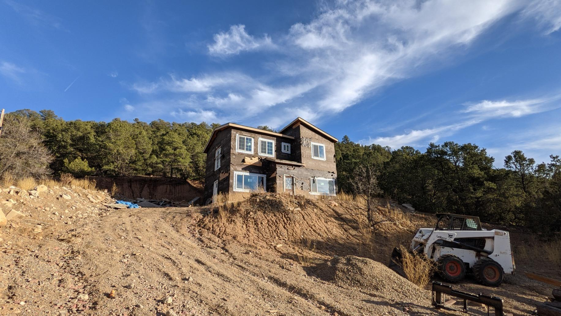 Great opportunity, perfect for contractors or anyone looking to customize their own mountain home!  Only a mile from I-40 and 10 minutes from Northeast Albuq.  The home has spectacular mountain views and approx, 2 acre lot for privacy.  (Being sold as is in it's incomplete status) Construction will continue until an offer is accepted, check for updated info.    2X6 construction, framed with windows and roof, Plumbing and electric is installed, should be permitted this week.   House is entirely electric, septic installed, 280 ft well with water at 70ft, roughly 10 gallon/min refill rate.  Well rights run with property.  Building permit pulled and is transferable.  Concrete slab and roof is green tagged.   Included in sale, mini split A/C 4 zones, bamboo flooring and bathroom vanities.