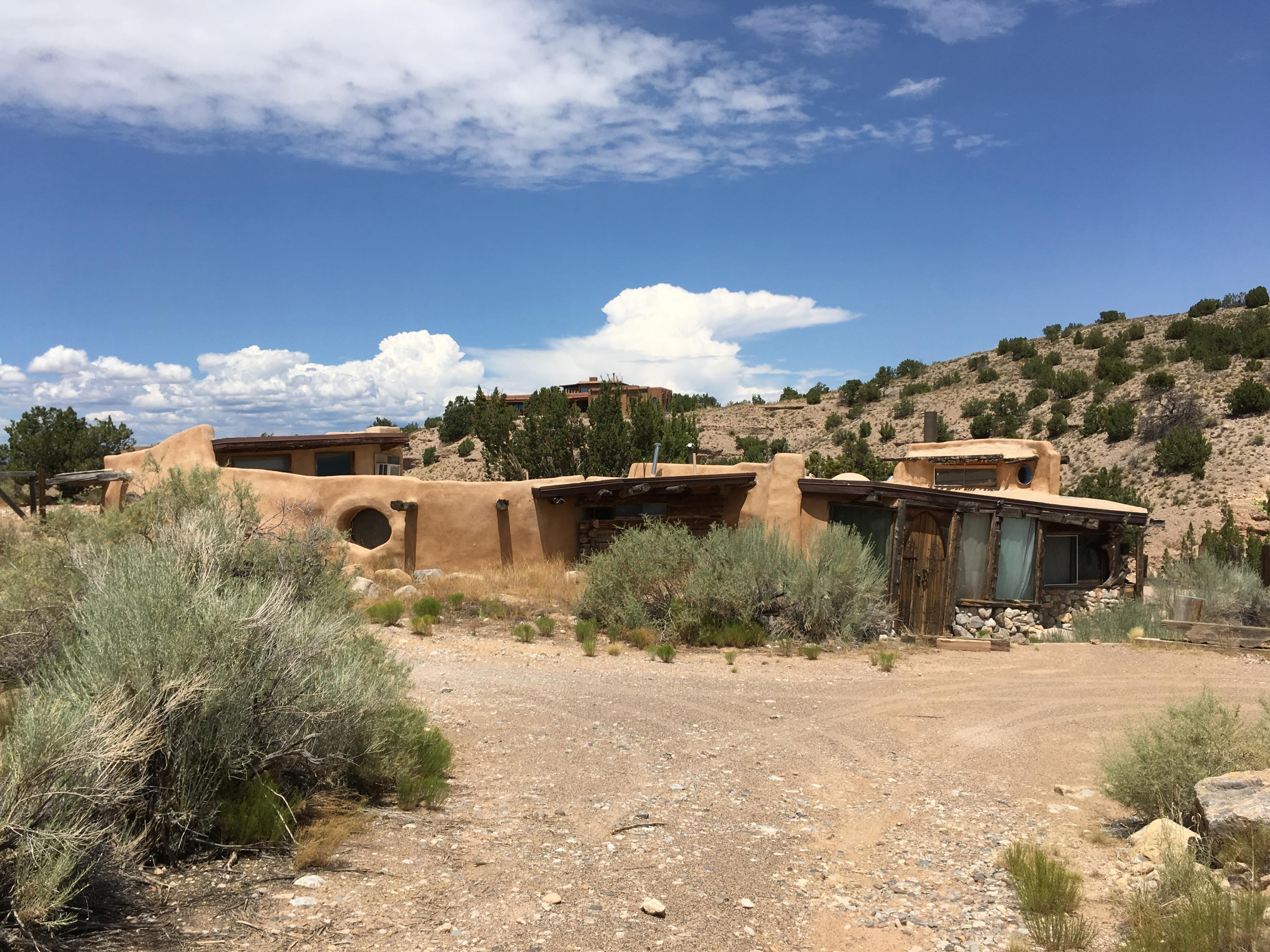 Unique adobe structure designed and occupied by renowned architectural designer Ivor Williams.  His career included projects in NM, Hawaii, NY and he was studied by the University of Oklahoma for his innovative and bold designs.  In true Williams style, this house feels more like walking through a 3-D sculpture, full of curves, levels and planes.  He has always dared to do things that others only think of, ie an outdoor shower, a sunken bedroom with rock walls, trees left intact even if they are growing through the house!  His ingenious use of raw materials evokes a rustic, organic appeal that is like none other and is perfect for the person with vivid imagination and creativity.  Bathroom and kitchen can be finished to your design..