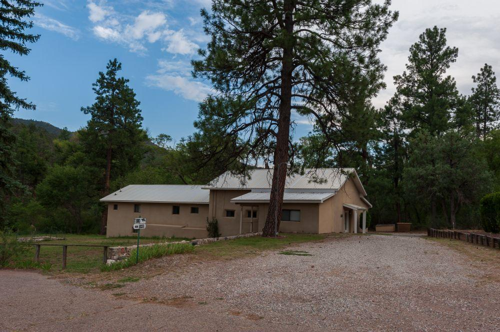 Situated in the heart of majestic Jemez Springs, New Mexico, this quaint 5 bedroom /4 bathroom home sits on 5.09 acres of lush and usable land surrounded by fruit trees and grass. Bordering Highway 4 to the West, the property has the Jemez River flowing through the property, as well as a long lived acequia waterway. Surrounded by dramatic valley views and evergreen tree laden mountain-scapes, wildlife and native birds can be seen traversing the scenery. There is adjacent acreage and homes available for sale. Jemez Springs is best known for its nearby and off-property natural hot springs warmed by the ancient waters of the Valles Caldera. The property is just an hour drive away from the larger city of Los Alamos or Bernalillo/Albuquerque.