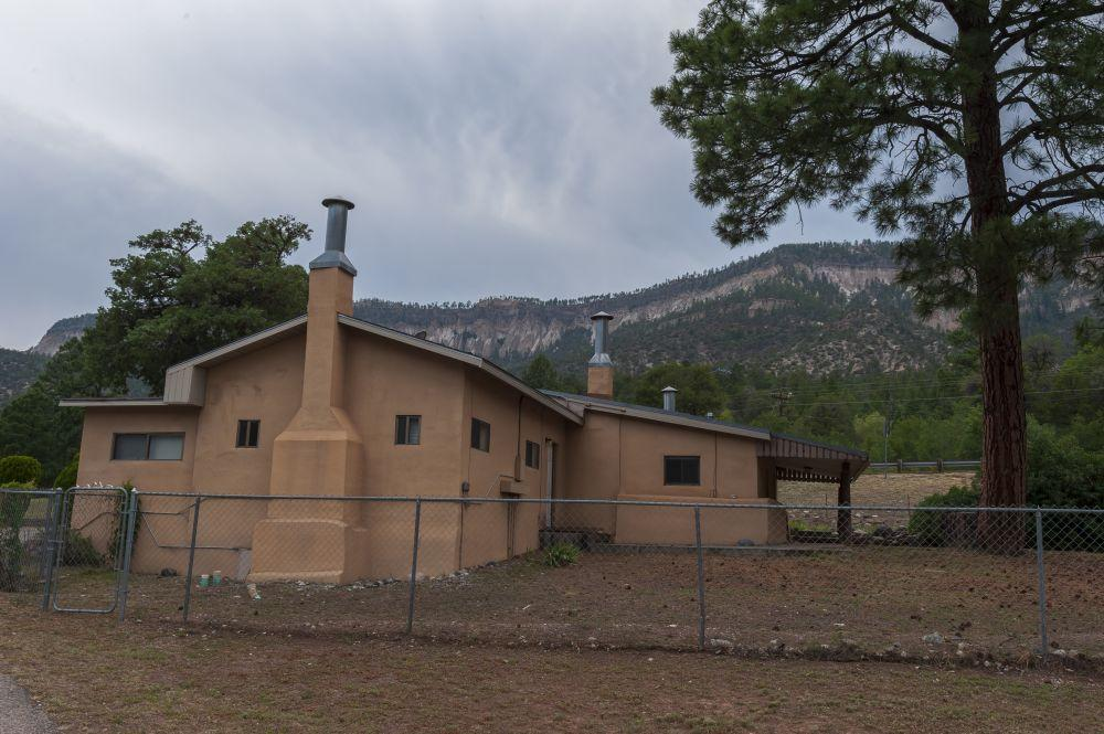 Situated in the heart of majestic Jemez Springs, New Mexico, this quaint 2 bedroom, 2-1/2 bathroom home sits on 2.7 +/- acres of lush and usable land surrounded by fruit trees and grass. Bordering Highway 4 to the West, and the Jemez River to the East, the property also flanks a long lived acequia waterway. Surrounded by dramatic valley views and evergreen tree laden mountain-scapes, wildlife and native birds can be seen traversing the scenery. There is adjacent acreage and homes available for sale. Jemez Springs is best known for its nearby and off-property natural hot springs warmed by the ancient waters of the Valles Caldera. The property is just an hour drive away from the larger city of Los Alamos or Bernalillo/Albuquerque.