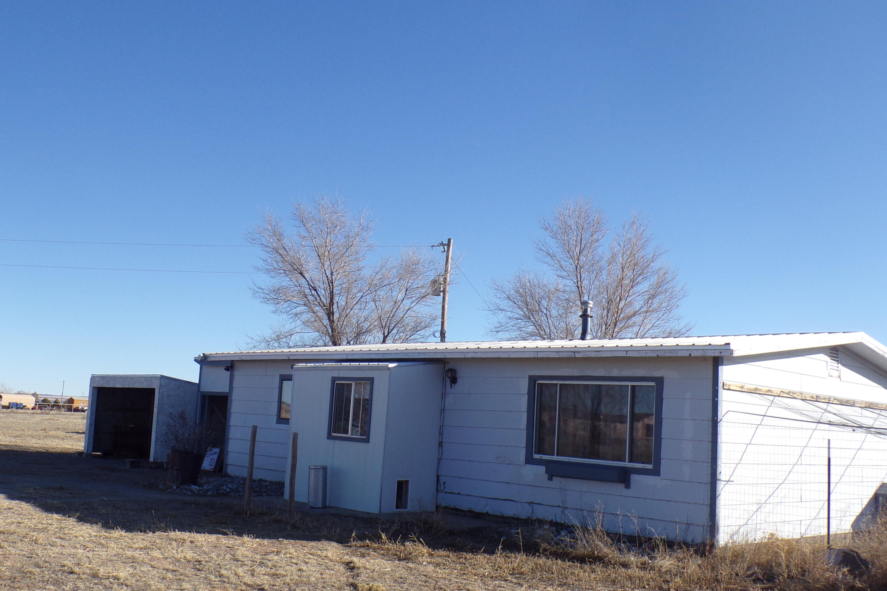 This Moriarty, NM country home on 5 acres is fully fenced and is an easy commute to either Albuquerque or Santa Fe. The home has new wood laminate flooring throughout, fresh paint and a partial kitchen upgrade.  The 976 sf consist of 2 bedrooms and 2 bathrooms and would make a nice cozy home for two or three people. Outside there is a carport and storage area, horses are allowed and not to be missed are the beautiful mountain views that feature the Southwest famous sunrises and sunsets. Just 35 minutes to Albuquerque.