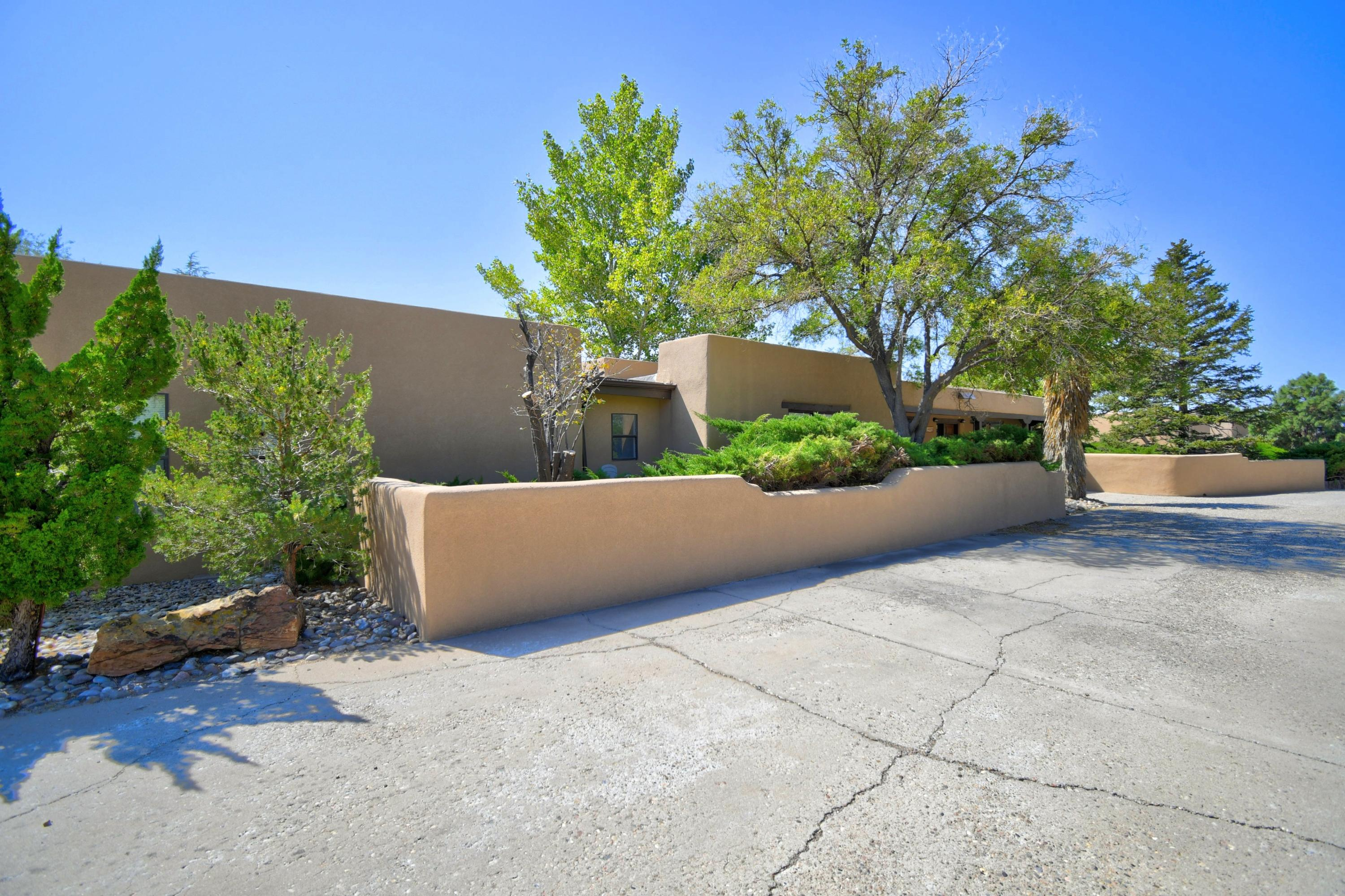 Located in the foothills with easy access to I-40, this beautiful adobe home features 6 bedrooms and 6 bathrooms, has all brick floors, wood beam ceilings and beautiful Mexican tile countertops for a warm and unique home. A private yard complete with a waterfall feature pouring into the sparkling pool, is completely secluded with mature landscaping and walled backyard. Multiple, cozy living spaces provide the option for an in-law suite or multigenerational living. An oversized garage and large workshop, a great amount of room and more storage on the side. Kitchen has stainless steel appliances and a distinctive wood burning fireplace. Living and dining room flow together with a kiva fireplace, natural light and cozy, yet spacious living. renovated by two architects. MUST SEE