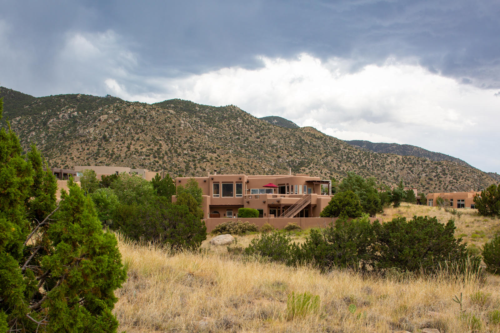 This exceptional High Desert home is perfectly positioned to take advantage of the dramatic views of the Sandia Mountains and city lights. Beautiful outdoor living spaces feature multiple decks, patios, an outdoor kitchen, a resort style pool, an outdoor Kiva fireplace, and grassy yard, a rare find in High Desert. Inside, there are 2 living and dining areas, a huge game room, an exercise room, 6 bedrooms, and a home office. The generous size of this home offers a flexible floor plan that would work for a variety of living arrangements. Classic Southwestern detailing such as Vigas, wood and tile flooring, and Kiva fireplaces give this home charm and character. Enjoy the best of the High Desert lifestyle with walking, biking and hiking trails immediately outside your front door!