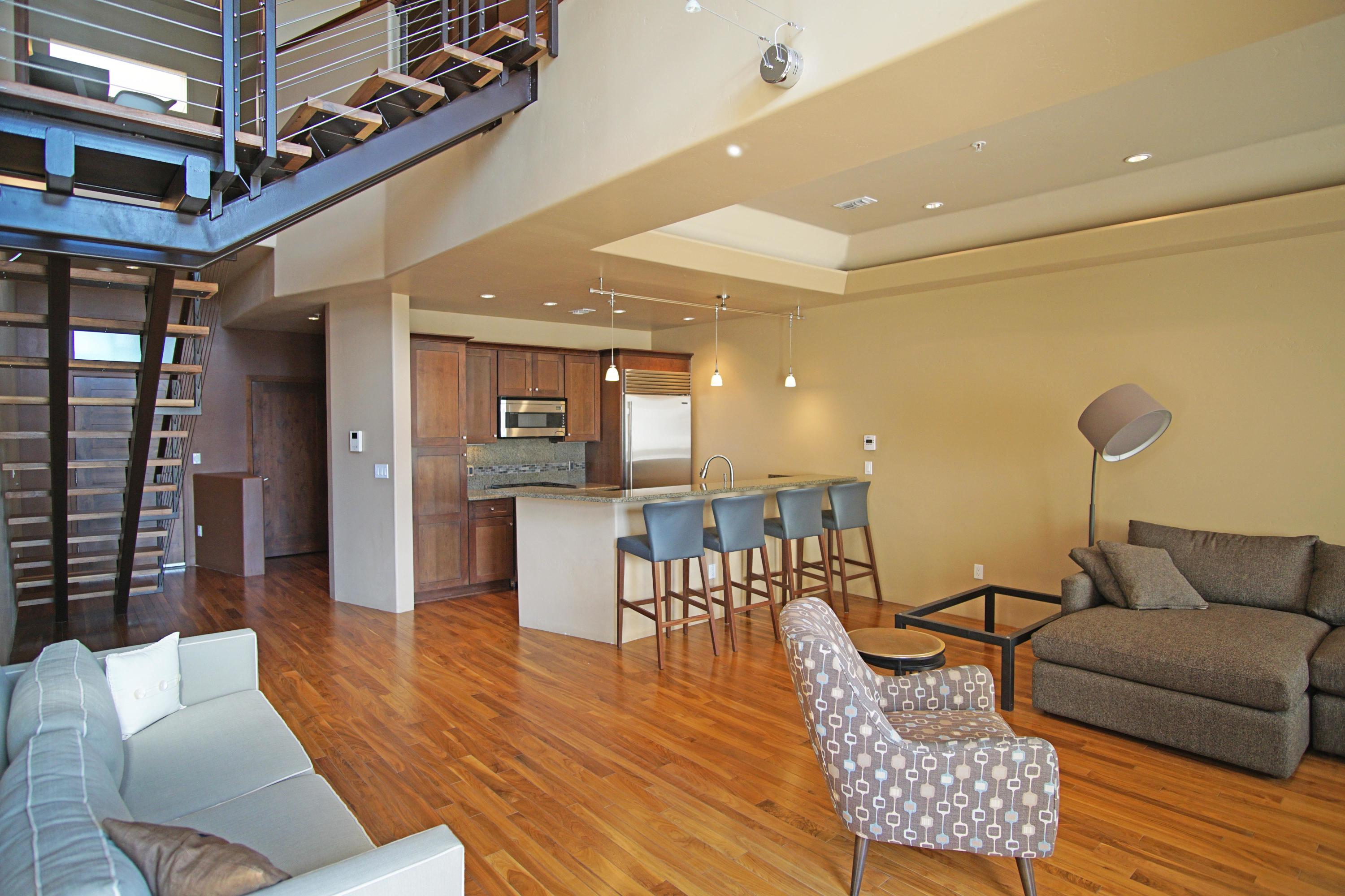 PRICED TO SELL QUICK!!  Super Clean, has that new house smell... Includes 2 car garage. Will NOT last long.. ''The Place at Nob Hill'' offers luxury living in the heart of Nob Hill, this contemporary style condo with 1 small balcony that faces south giving the owner(s) a spectacular view of Nob Hill. The natural light shines through the open floor plan with real wood floors. Stainless steel Wolf appliances in the kitchen with granite counter tops, while the living room is wired with surround sound. The master bedroom features a custom closet with built in shelves to maximize the space. The 2nd bedroom has an attached full bath. This unit has a 2 car tandem garage, right in the heart of Knob Hill near shops, restaurants, breweries, studios, UNM, hospitals etc. what a great location!!