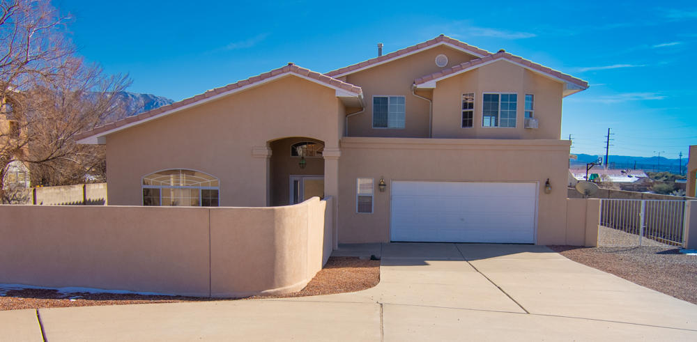 Freshly painted throughout! Spectacular Unobstructed views of the Sandias!! Enjoy soaring ceilings in a flexible floor plan. 2 living spaces both with gas log fireplaces. Eat-in kitchen AND formal dining space. Open/split staircase leads you to Master plus 2 additional BR. Additional views off of 2nd floor balcony. MB includes 2 closets, dual sinks, jetted tub & separate shower. Tile pitched roof, backyard access, spectacular private walled front courtyard. Multiple car owner will be jazzed about spacious circular drive and extra parking. Make this .5 acre oasis your next home!! $1,000 flooring allowance.