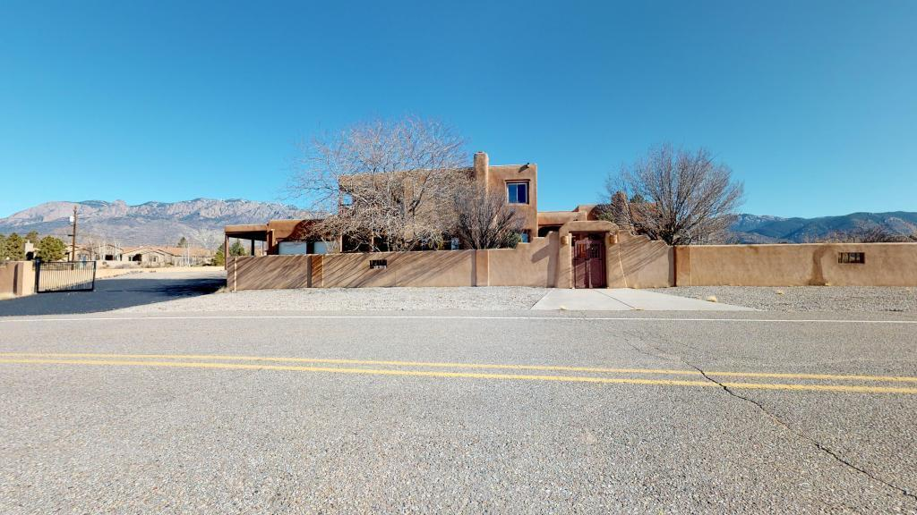Huge Adobe Estate situated on almost an acre in NAA. Views overlooking Tanoan as well as city and mountains! 6 bedrooms each with own bathroom plus office. Separate attached guest suite w/BR, bath, LR, Kitchen and private entrance.Beamed T&G ceilings, saltillo tile, nichos, built-ins, wetbar, 5 fireplaces, flagstone courtyard & more! Grass and fruit trees.Check out room sizes! Tons of storage, covered RV parking too!! Recently installed wood floors in master, family Room, and second BR on main level!!