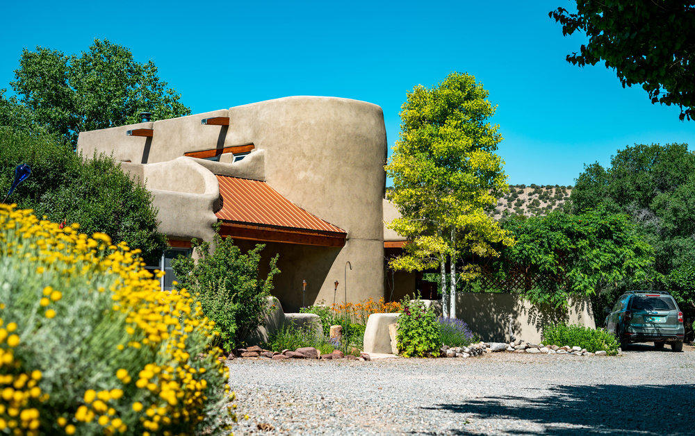 Unique custom designed and built home is an example of  the finest in adobe craftsmanship, located in a peaceful, quiet irrigated valley, with large south-facing windows that provide excellent solar gain  during the cold weather months, and they frame the lush walled courtyard and superb mountain views. Brick floors, hand-peeled vigas throughout, hand troweled plaster walls and hand-carved lintels and corbels. add beauty and charm.  In addition to ground level patio, the 13x13 deck off the master BR is perfect for viewing starry night skies. Horses, and other farm animals allowed. Mature fruit trees - apricot, apple and pear, are thriving, with fully xeriscaped front and back landscaping.