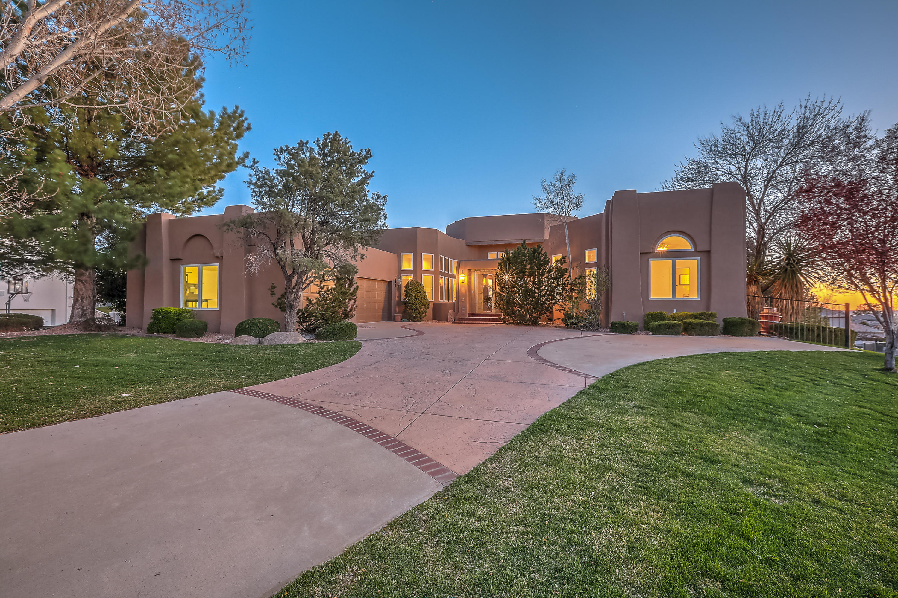 This incredible home sits on a large corner golf course lot in the luxury home subdivision of Sauvignon! You'll enjoy views of the Sandia mountains or plush green Tanoan golf course from almost every room in the house. The kitchen, stucco, windows, roof were all re-done in 2019. The open and bright kitchen has stainless steel appliances, granite, walk in pantry, desk area, island, breakfast nook, formal dining area and more.  The elegant master bedroom on the main floor has a large walk in closet, double sink vanity, a custom snail shower, jetted tub, fireplace, and an outdoor deck with views.  Downstairs is a large family room with 3 other bedrooms and 2 full bathrooms.  The outdoor space is cozy and inviting with several patio and deck areas, grass, trees, and access to the golf course.