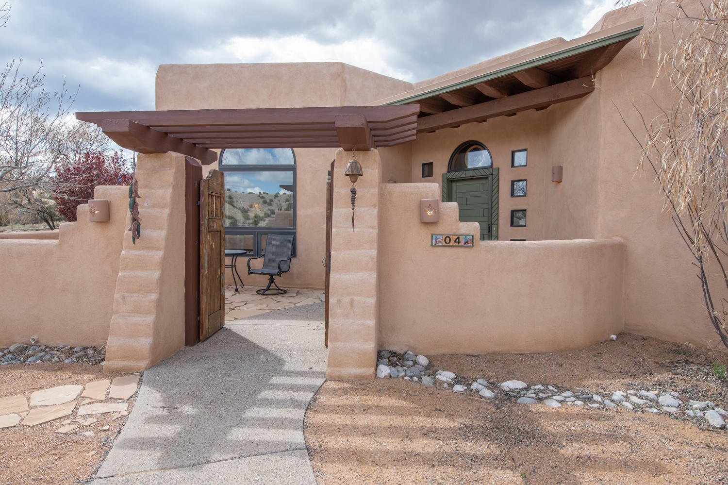 Santa Fe charm in a custom home on Placitas. Great views of colorful mesas providing maximum privacy on 1.41 acres. Enter your new nest through the protective front courtyard gates to a hand carved front door. Upon entering feel all cozy with authentic adobe walls, wood beams accenting the living and formal dining rooms. The kitchen features a huge center island, decorator colors, stainless appliances, big window with an even bigger view. A kiva fireplace is in the breakfast nook with sliding doors to the patio. More sliding doors in the living room offering access to the patio and another kiva fireplace. The master suite with views, huge closet, all new bath with sculptural deep soaking tub, and glass shower. You really can have it all here, plenty of patios. Plus a three car garage.