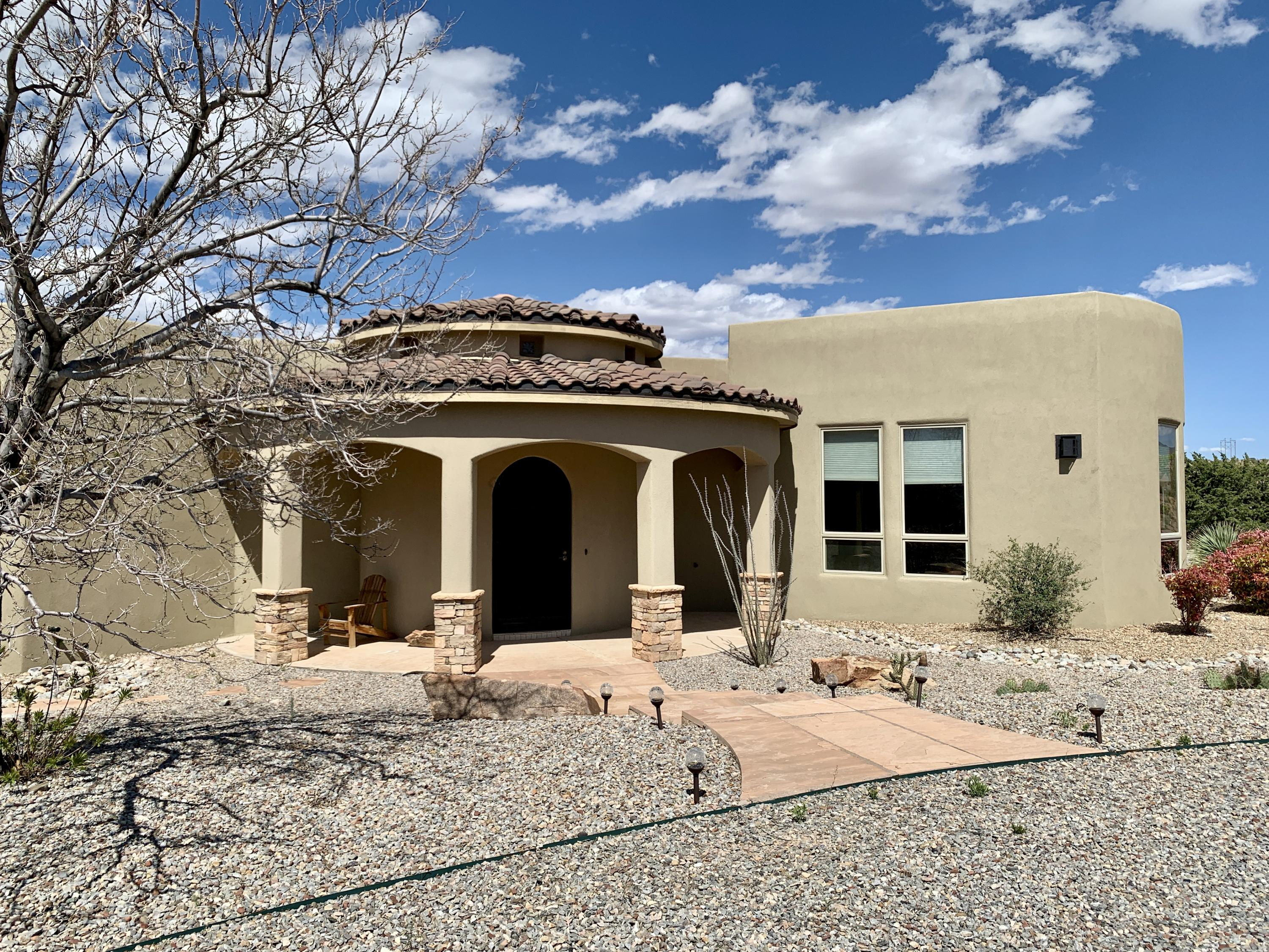 Price Reduced! Tranquility minutes from ABQ! Mountain and desert vistas from every window. SW and Old World architectural styles blended with current amenities. 3 BR + Office, 3 BA home. Gourmet center island kitchen w/ Thermador appliances, full-size range + built-in oven, wine fridge, prep area + sink, 2 dishwashers, custom dry bar + more. Finishes include Diamond Plaster, Travertine and tile throughout. Natural light and stacked stone highlight the deep spa tub and all-tile shower in the master suite. Perfect for 4 season outdoor living w/ stone fire pit, hot tub + shade trees. Grow your own food in the backyard orchard of mature, fruit-bearing trees (peaches, plums, nectarine, apple)  fully-automated irrigation system. Newly repainted Great room and Master Bed/Bath See Virtual Tou