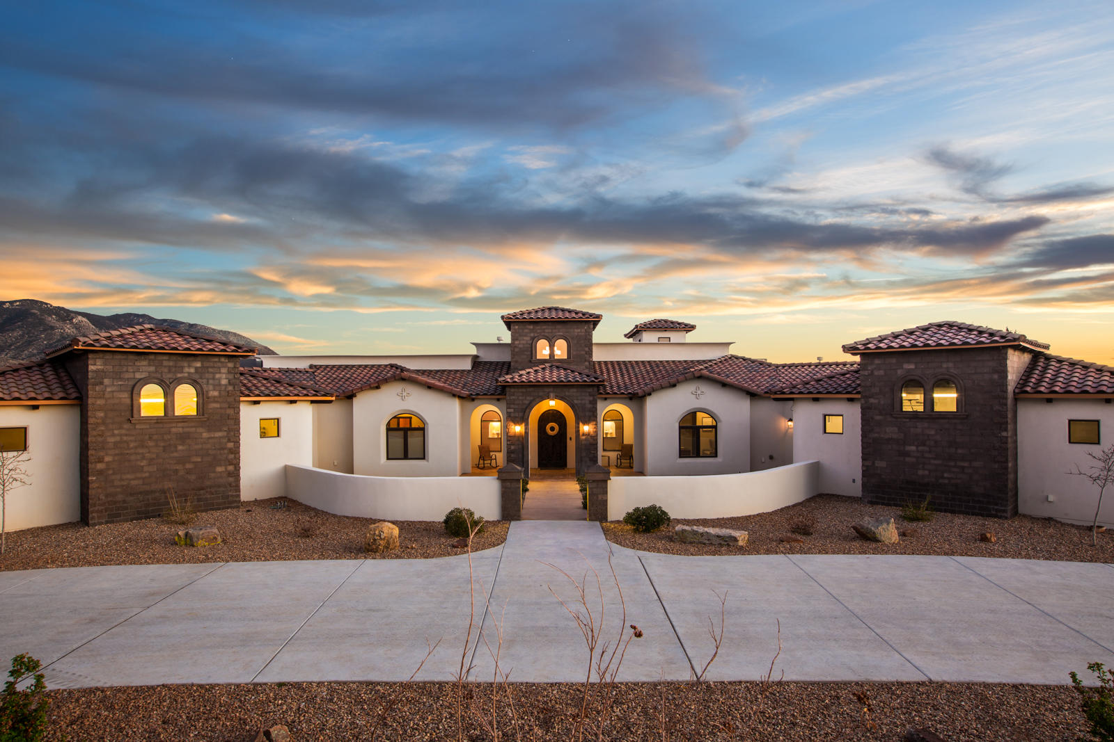 Luxurious Mediterranean Estate located in the prestigious North Albuquerque Acres on a gated .89 acre property. Quality of taste abounds the expansive floorplan hosting 4,662sf, 4 bedrooms, 3 baths, 2 living areas, office, gym and 4 car garage.  Fully equipped Chef's kitchen w/ designer cabinetry, granite countertops, built-in oven/microwave, 6 burner gas cooktop, pot filler and a family style island with seating. Dining with custom built in bench. Living area w/ beautiful ceilings and a custom fireplace. Glamorous master retreat with 2 sided fireplace!  Spa-like bath w/ his/hers vanities, custom mirrors, free standing tub, fireplace, walk-in shower with dual heads. Boutique style closet with dressing area, island and washer/dryer! Covered patio w/ outdoor kitchen & fireplace with views