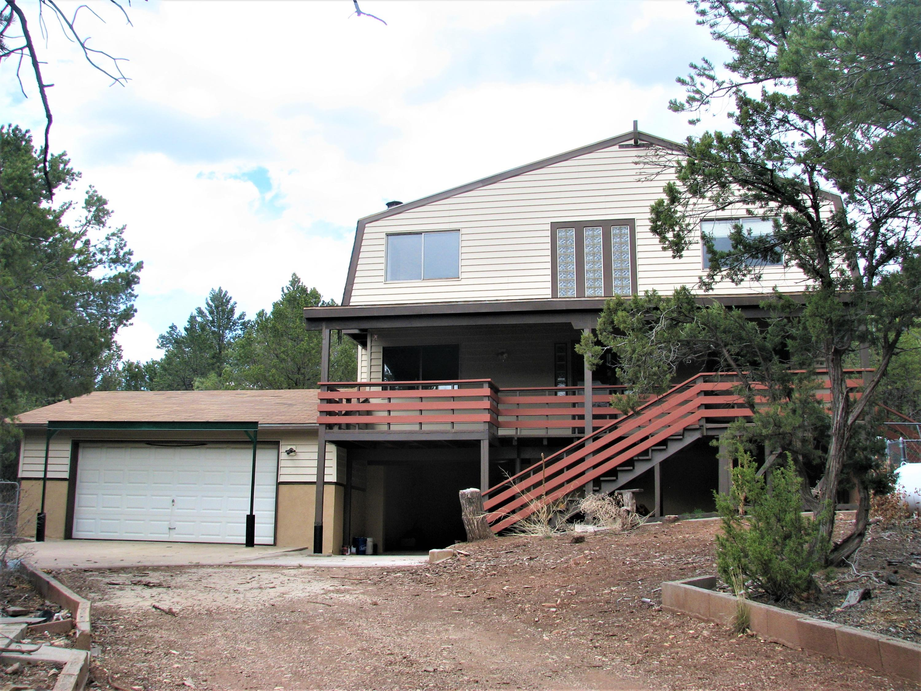 Awesome Mountain Getaway!Nestled among the Ponderosa Pines in the tiny New Mexico mountain community of Jemez Springs, this home is on a corner lot in the quiet, secluded and  scenic,  a mile north of Soda Dam.  Newly refurbished, with laminate flooring throughout.  A new septic system. Bathed in natural light,  a circular staircase, a 30 foot front porch with breathtaking views upstairs and downstairs. The home features three heating sources: a wood-burning stove, propane wall heater, and baseboard heaters and four ceiling fans. The large two-car garage is well-lighted,  and  an attic and shelving for a large home workshop, & Carport! The unfinished basement utility room has washer/dryer hookup, water heater, and is stubbed for a third toilet. Fenced. One mile walk to the riv