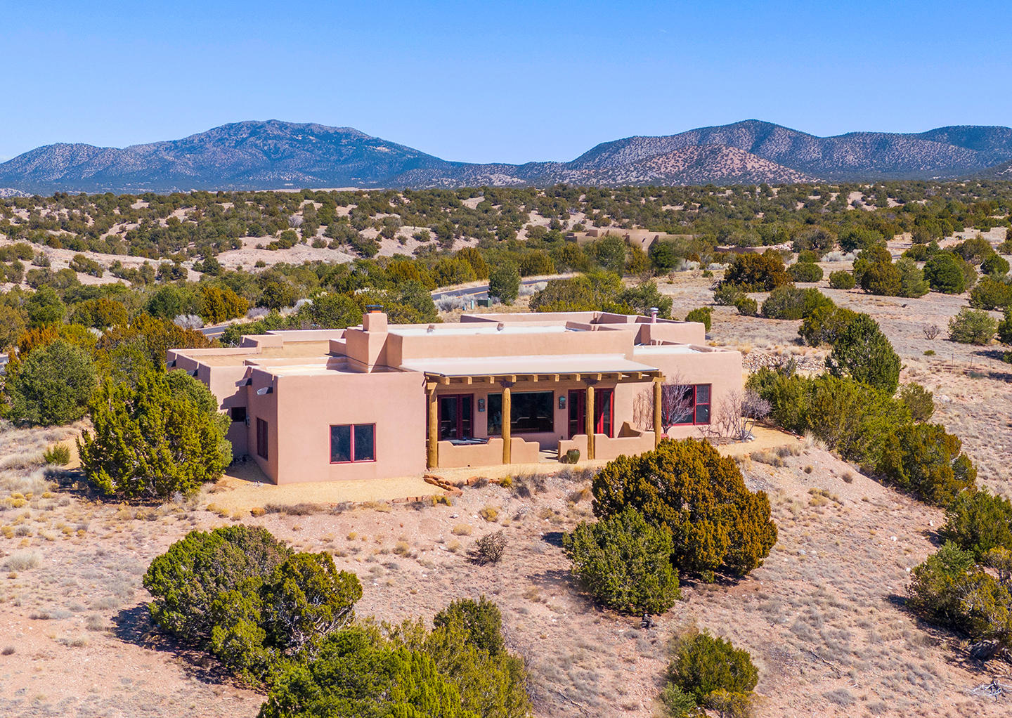 Finally, relax in the quiet, guarded & gated, discrete premier mountain neighborhood of San Pedro Overlook. Offering stunning Sandia mountain views this authentic modern-day adobe-style home will have you in awe at every turn. Constructed with thick E-crete walls this hypoallergenic home incorporates multiple-green features. Open floor plan offers plenty of space for everyone and includes two large living areas, office, and 3 bedrooms each with their own en suite bathroom. The gourmet chefs kitchen equipped with Viking professional appliances, large center island, and ample cabinetry is open to the great room and allows for easy entertaining. Other features include colossal viga ceilings, Alder doors throughout, built-in bookcases, covered patios, and a serene front entry courtyard.