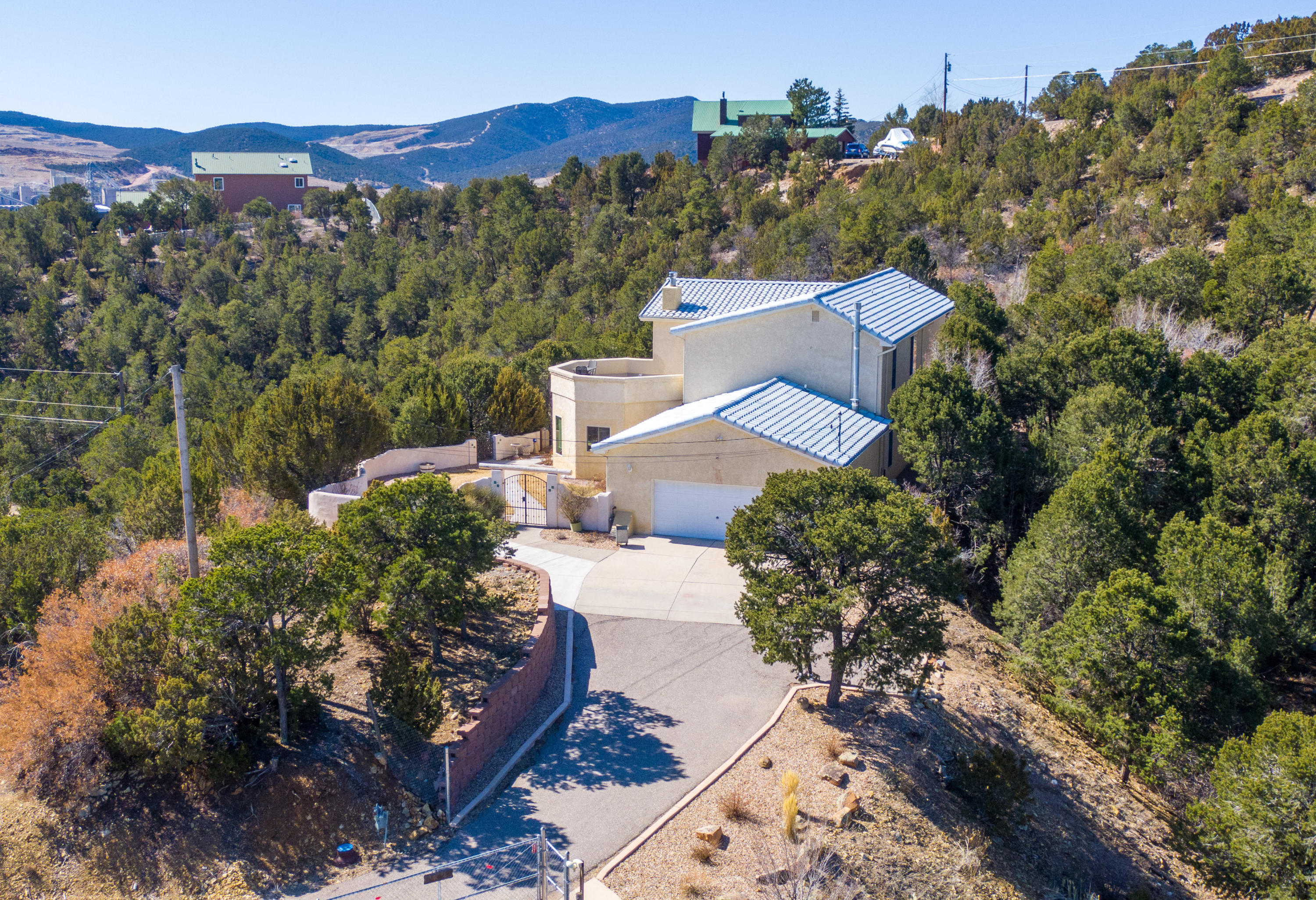 This beautiful mountain retreat is located in the Village of Tijeras & is only 8 minutes East of ABQ. The home sits on over 2 acres & is completely fenced in offering 360 views! Walk in & enjoy the grand stair case & vaulted ceilings. The home has an updated kitchen with gorgeous knotty cabinets, stainless steel appliances, corian counter tops & plenty of storage/pantry space. Upstairs is a master retreat with 2 lofts, his & her closets, free standing tub, double sinks, a makeup vanity & its own balcony! The yard is landscaped with garden beds & grass areas that are hooked up with automatic sprinklers/bubble & a Tuff shed. Notable features: central vacuum, over-sized garage, refrigerated air, tile roof, a wood burning stove, kiva fireplace, and newer windows/doors from Renewal by Anderson!