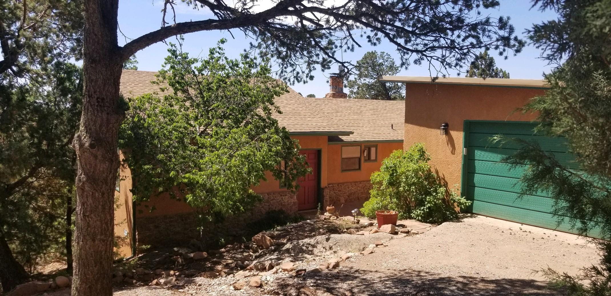 This property, located in the historical Old Sandia Park area, began as a summer cabin in the East Mountains in the early 1940's, then became a year-round home early 1950's. Tucked in next to the Cibola National Forest, there is hiking, snow shoeing, horse trails, and just 6 miles from Sandia Peak Ski area.  Come spring lilacs & iris are in bloom, summer offers a harvest from the fruit trees, fall is golden when leaves turn & hot air balloons are soaring.  Sit with a morning cup of coffee as the sun warms the large sunroom on a brisk winter's day & ward-off the evening chill with a fire in the wood stove or the fireplace - this home stays cozy from the passive solar gain. 1.75 treed acres, a new septic system, & a member of the community water system, make this mountain home complete.
