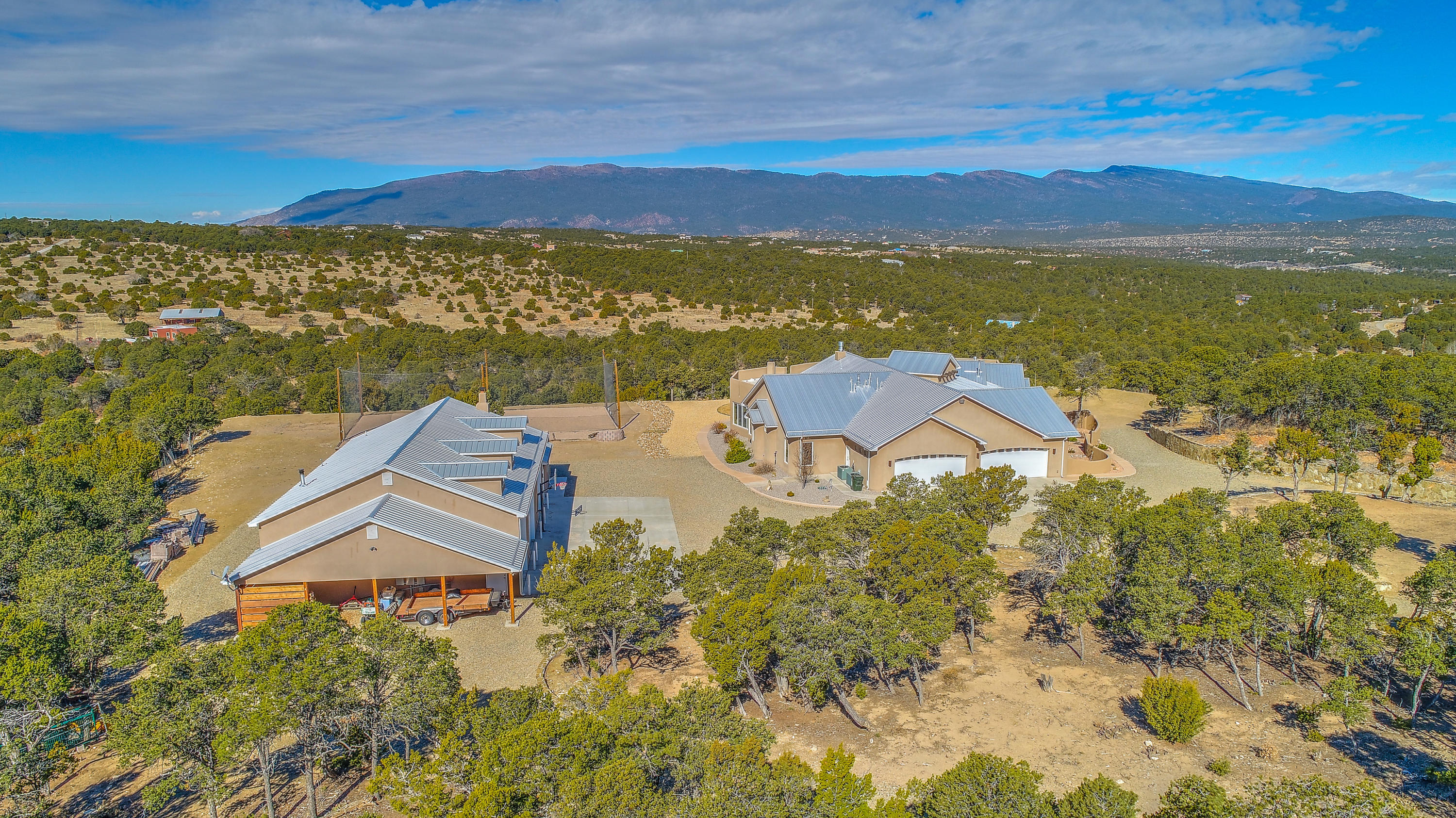 Spectacular views surround this exceptional custom home on 7 plus private acres just 25 minutes from ABQ international airport off of I-40. Main home with four bedrooms, three bathrooms, home office and wet-bar. Full guest house and RV garage. Thermador appliances in a chef's kitchen with double ovens, 6-top gas stove, warming drawer and built-in refrigerator. Walk-in pantry and extensive cabinetry provide plenty of storage. Eat-in kitchen and breakfast bar as well as separate dining room for formal dinners. Bring the party outside to the extended patio, fire-pit, and volleyball court.Ambiance exudes throughout this high-end home including on-demand hot water, gas fireplaces, radiant floor heating, refrigerated air conditioning and central vacuum.